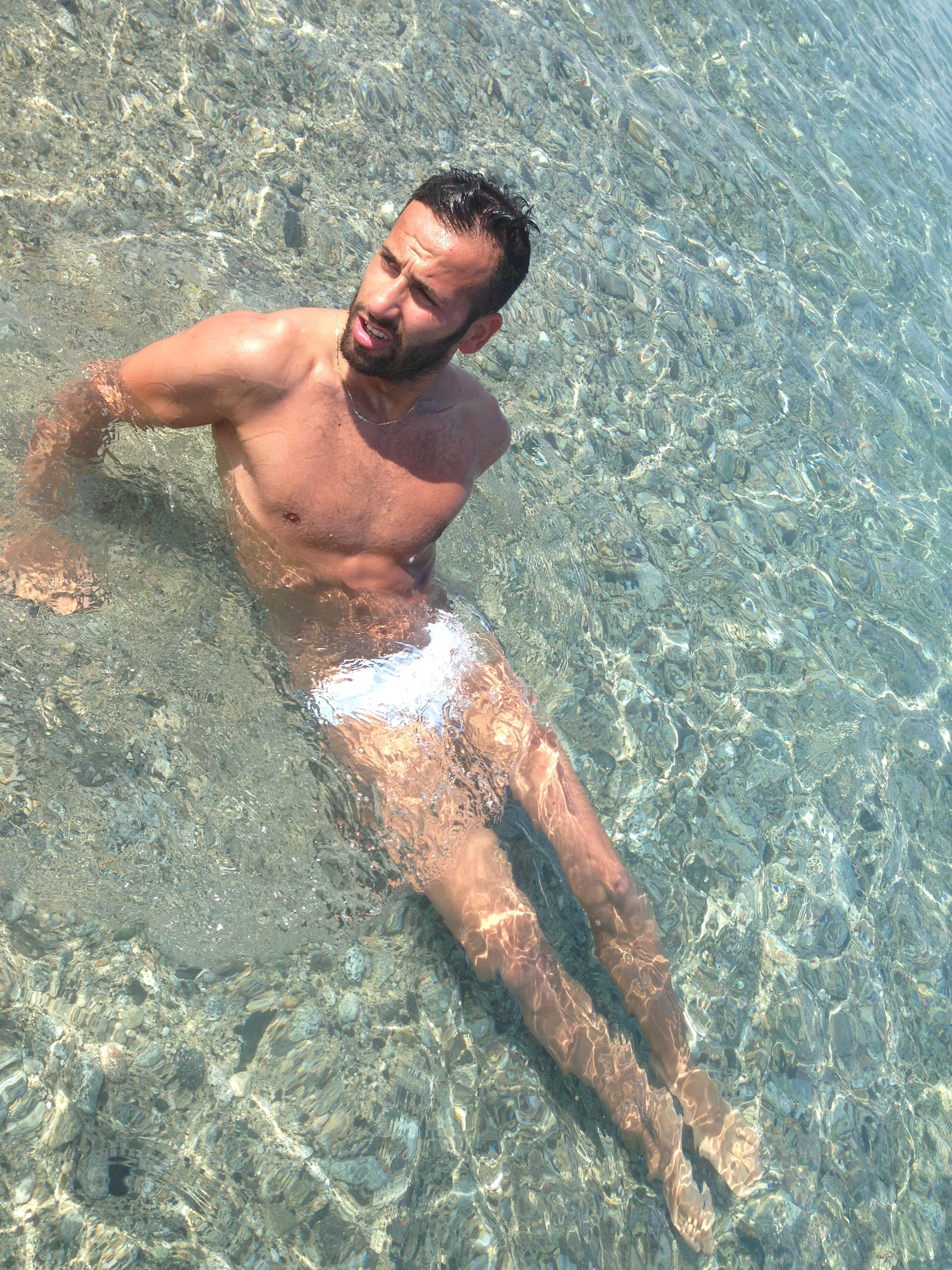 water, high angle view, beach, sea, lifestyles, leisure activity, shore, relaxation, sand, shirtless, wet, day, vacations, sunlight, outdoors, barefoot, nature, surf