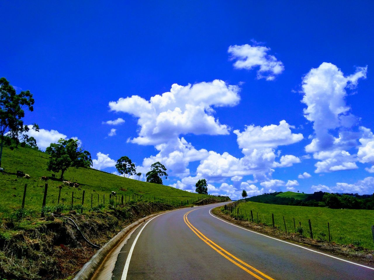 Road Amidst Green Landscape Against Blue Sky