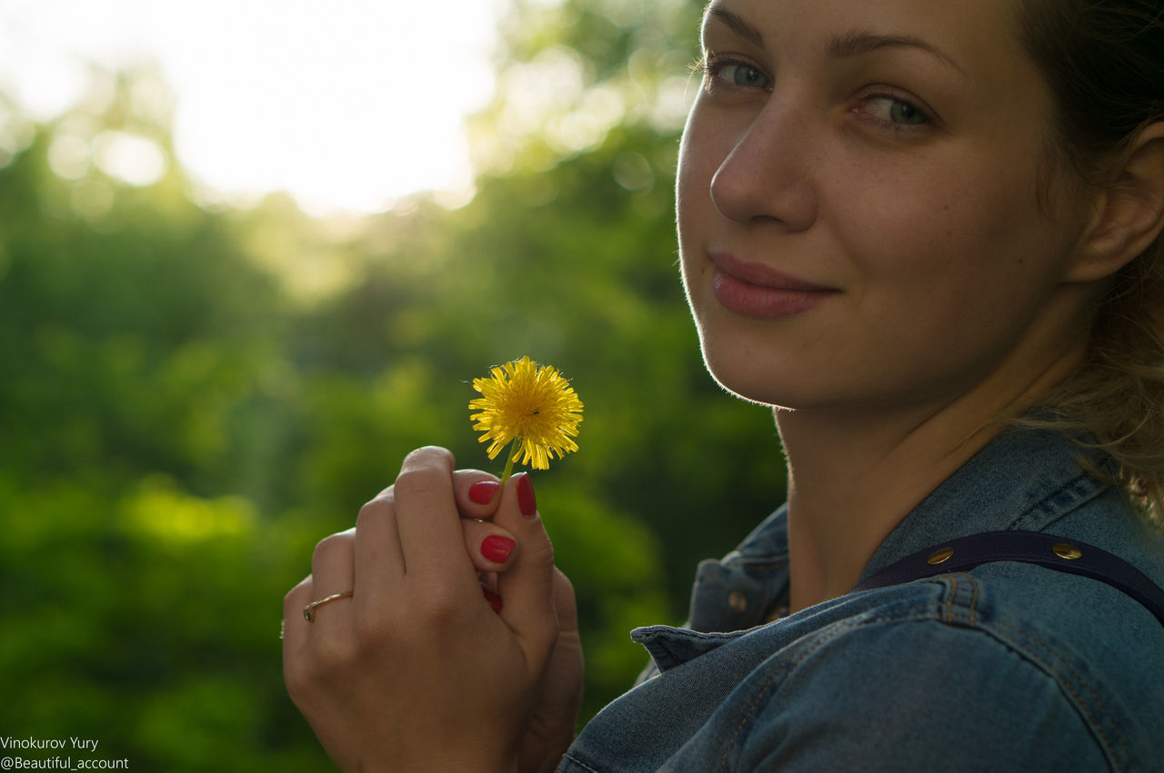 real people, flower, one person, leisure activity, lifestyles, young women, focus on foreground, day, nature, headshot, yellow, young adult, outdoors, close-up, holding, human hand, women, human body part, beauty in nature, fragility, freshness, flower head