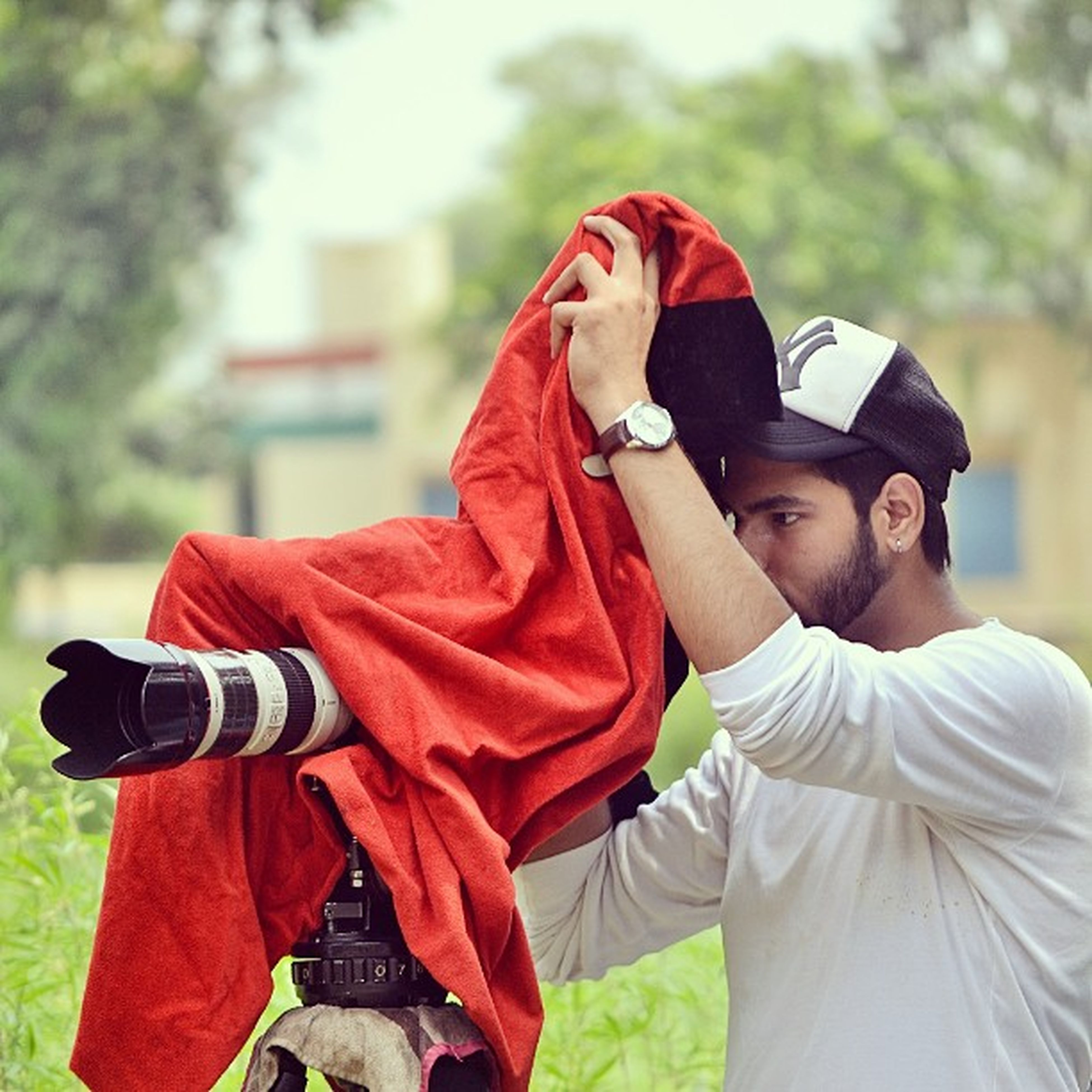 lifestyles, casual clothing, focus on foreground, person, leisure activity, young adult, front view, warm clothing, portrait, jacket, looking at camera, red, smiling, three quarter length, holding, young men, hood - clothing, waist up