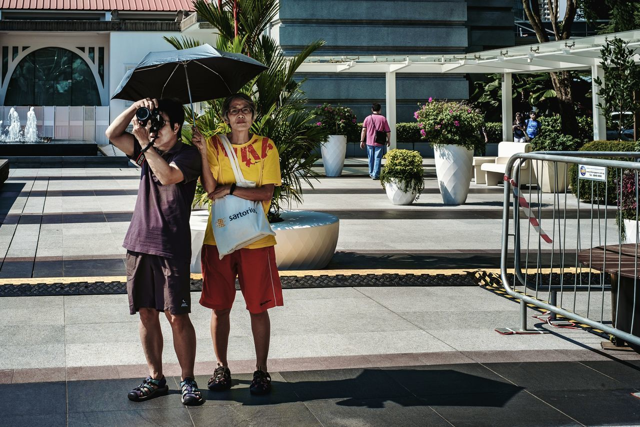 You know you are not successful until you have a woman to shelter you with a umbrella. Two People Togetherness Bonding Full Length Outdoors Friendship Adults Only Day People Friend Taking Photos Umbrella Sunny Shelter Shade Street Photography Streetphotography Streetphoto_color Streetlife Street Life Everybodystreet Fujifilm X-Pro1