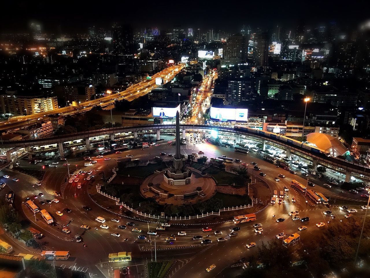 illuminated, night, architecture, city, traffic, built structure, high angle view, building exterior, light trail, connection, traffic circle, outdoors, road, cityscape, no people, high street