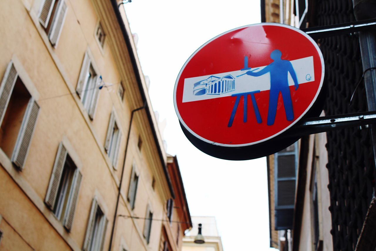 Art Is Everywhere The street signs in Roma even have a little bit of art to them. Rome Rome Italy Italy Graffiti Graffiti Art Low Angle View Road Sign Communication Building Exterior Architecture Circle Guidance Built Structure Day Text Outdoors No People City Close-up Sky