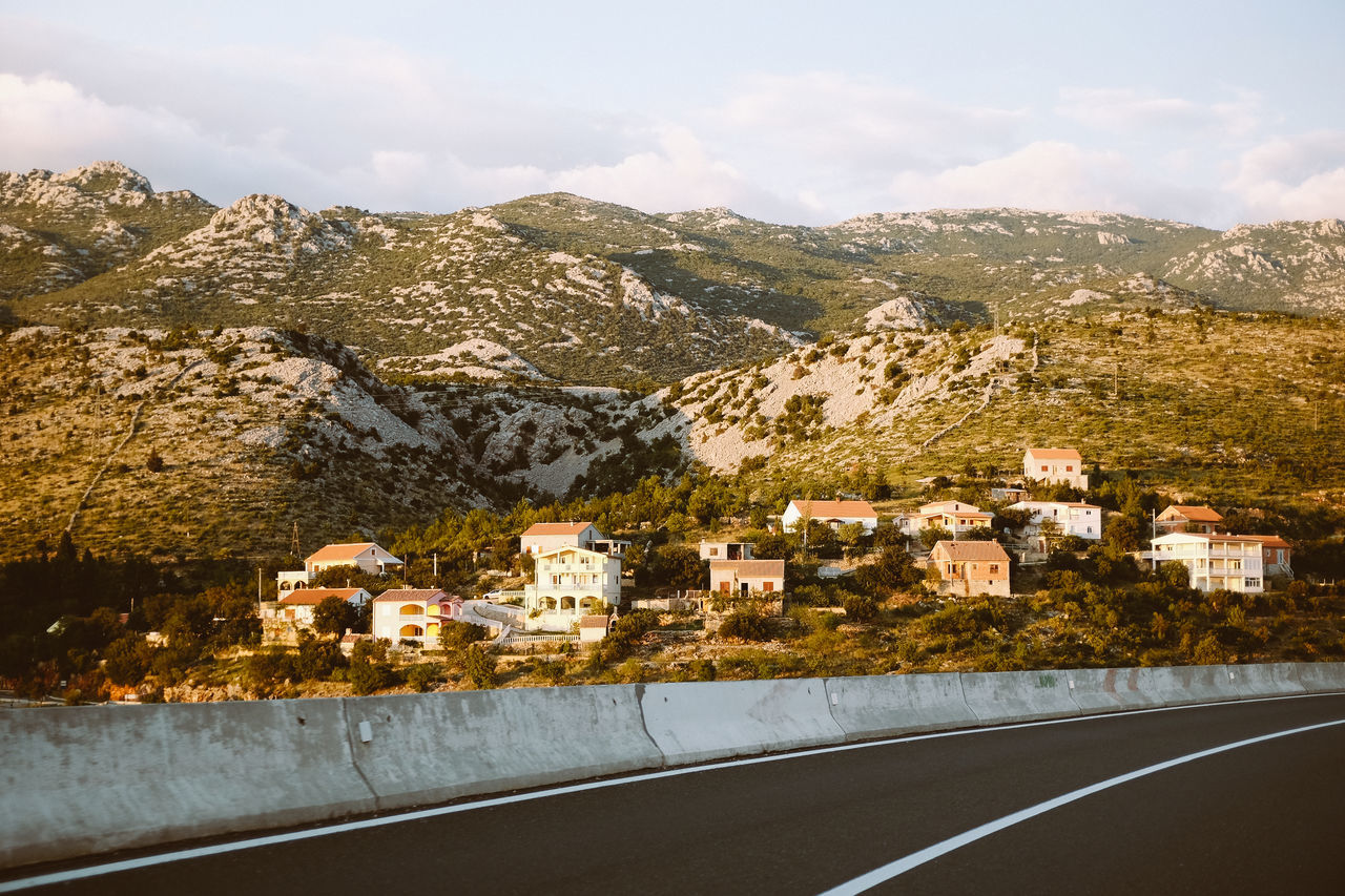 Mediterranean village with mountains in the background Architecture Building Exterior Built Structure Day House Mountain Mountain Range Mountain Road No People Outdoors Residential Building Road Sky Travel Travel Destinations Village