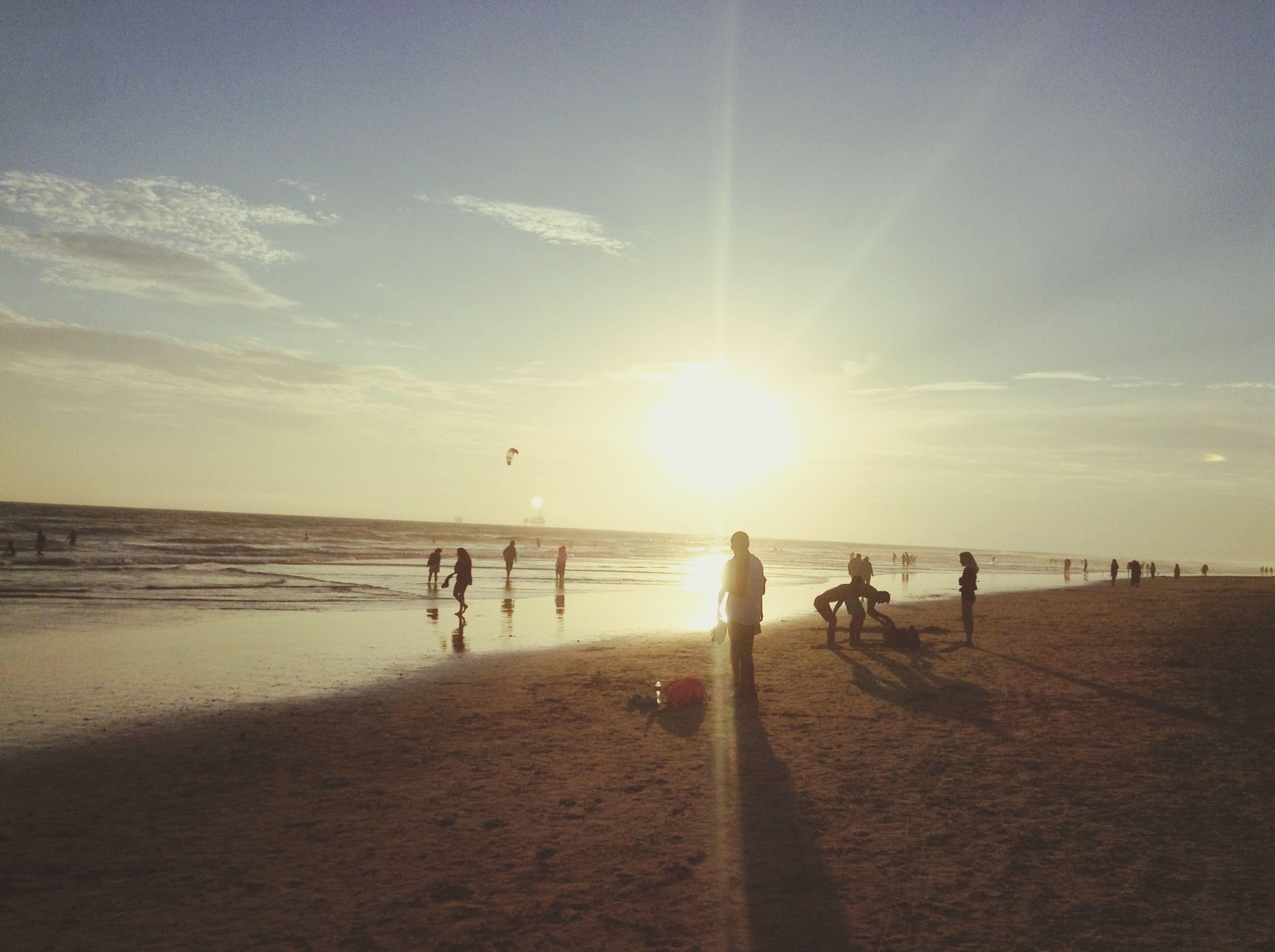 sea, beach, water, sun, horizon over water, leisure activity, shore, lifestyles, sunlight, sand, sunset, sky, vacations, sunbeam, large group of people, scenics, men, medium group of people, person