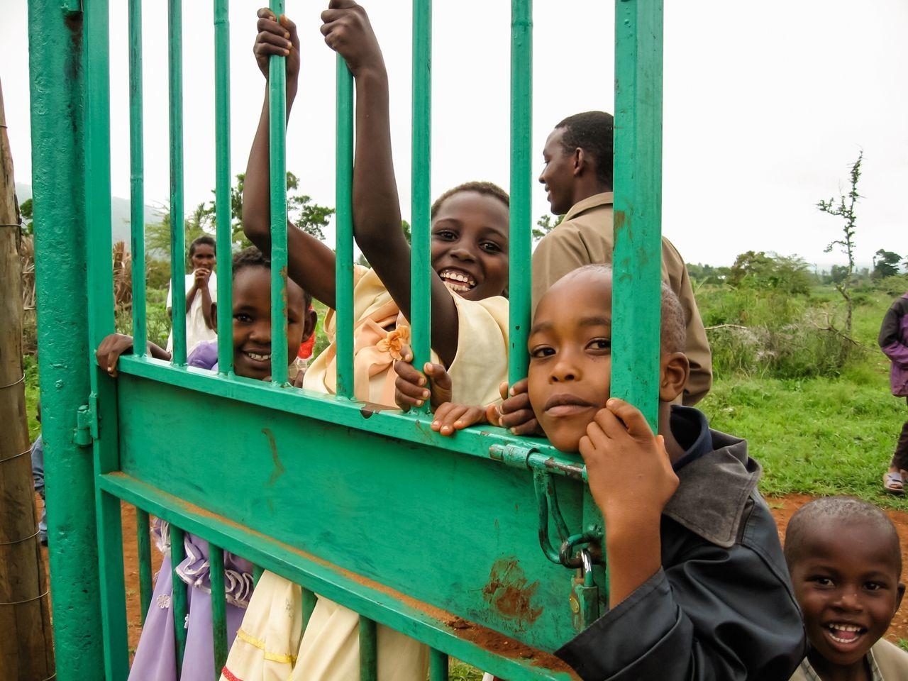 Kids Kids Being Kids Kid Children Curious Curious Kids Take My Picture Kenya Kenyan Kenyan Children Africa African African Children African Children Smiling Shy Gate Green Gate Swing From Gate Sunday Best Sunday Dress