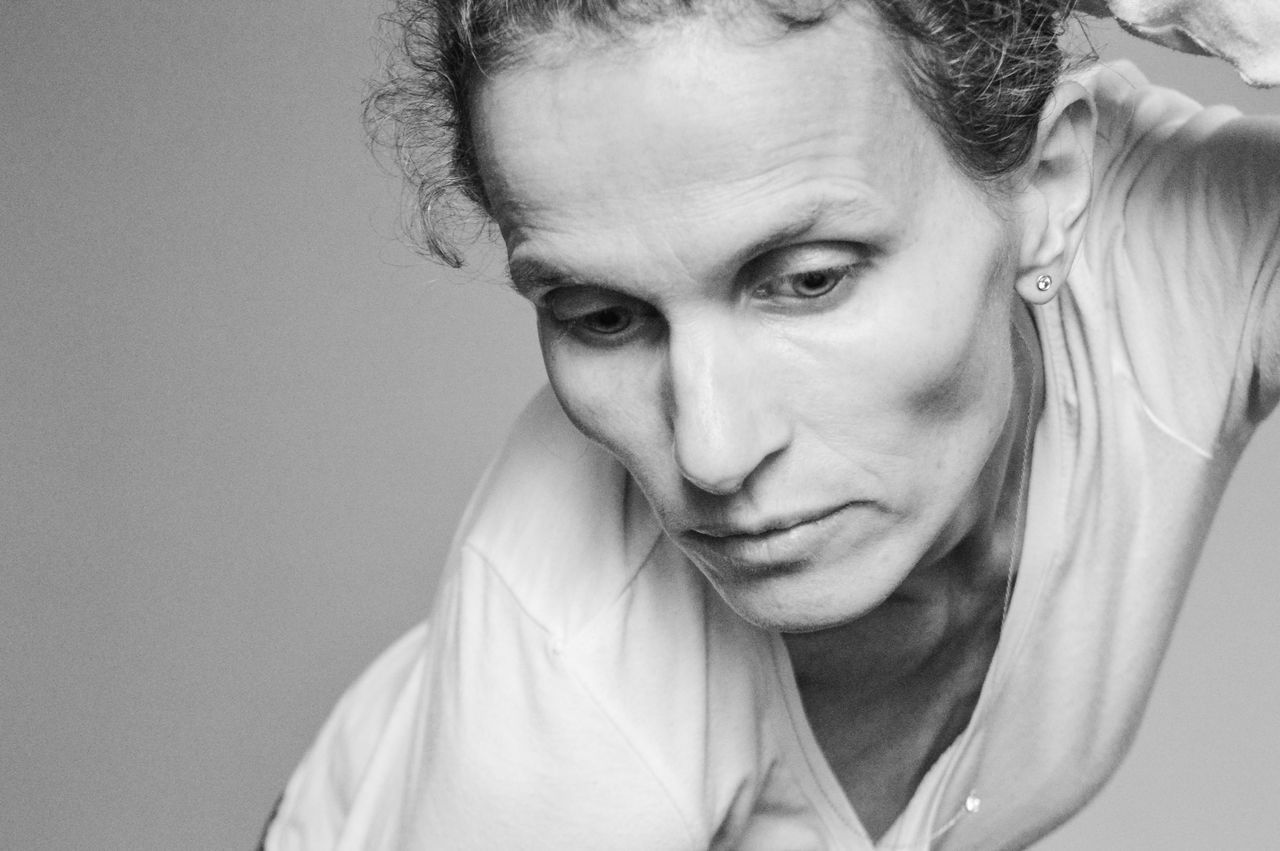 Black and white image of woman in white top Close-up Day Front View Headshot Human Eye Human Face Human Hand Indoors  Looking At Camera Mature Adult One Person People Portrait Real People Studio Shot White Background The Portraitist - 2017 EyeEm Awards
