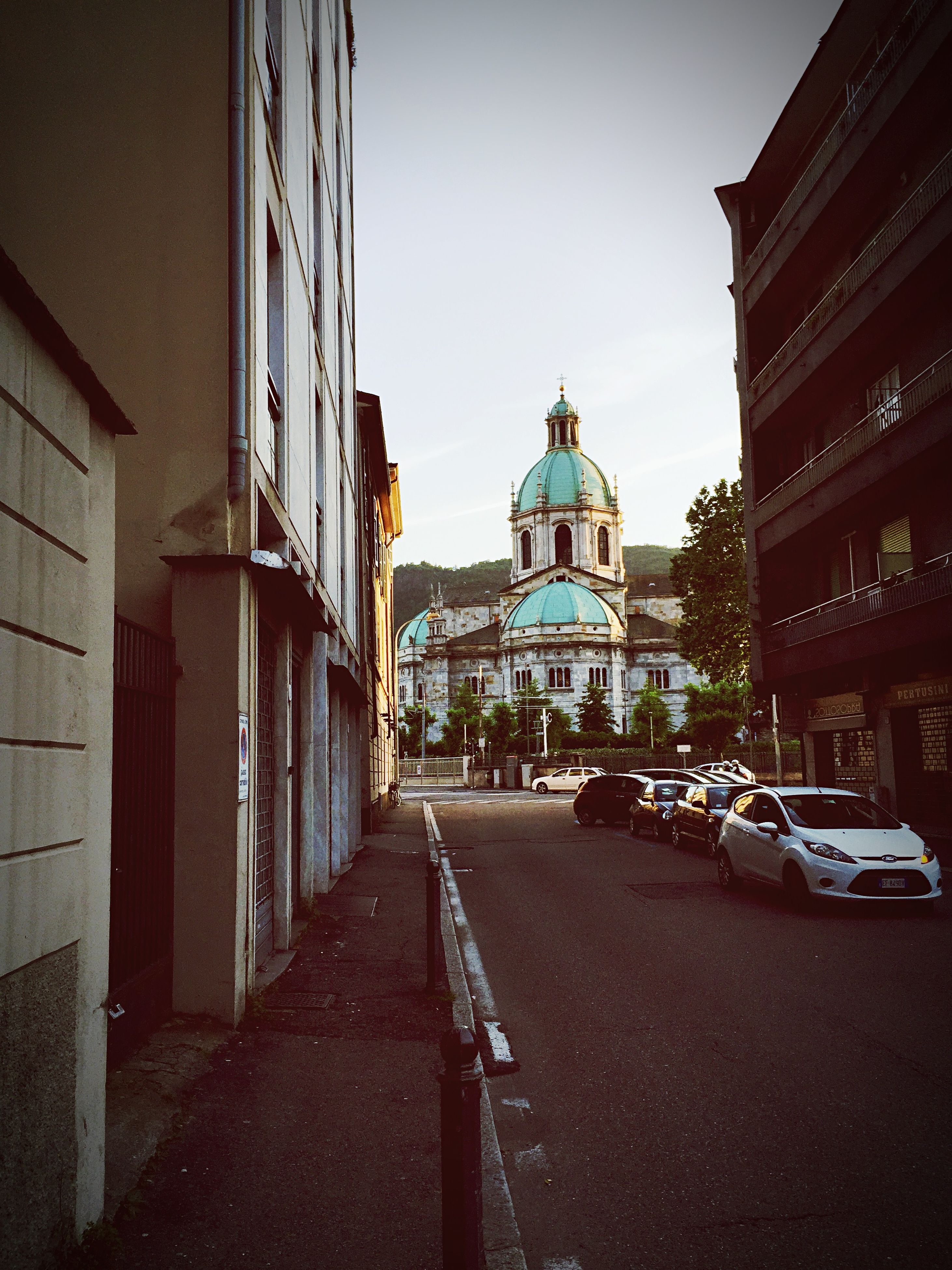 architecture, building exterior, built structure, the way forward, street, diminishing perspective, sky, church, religion, vanishing point, road, city, place of worship, empty, cobblestone, walkway, outdoors, spirituality, day