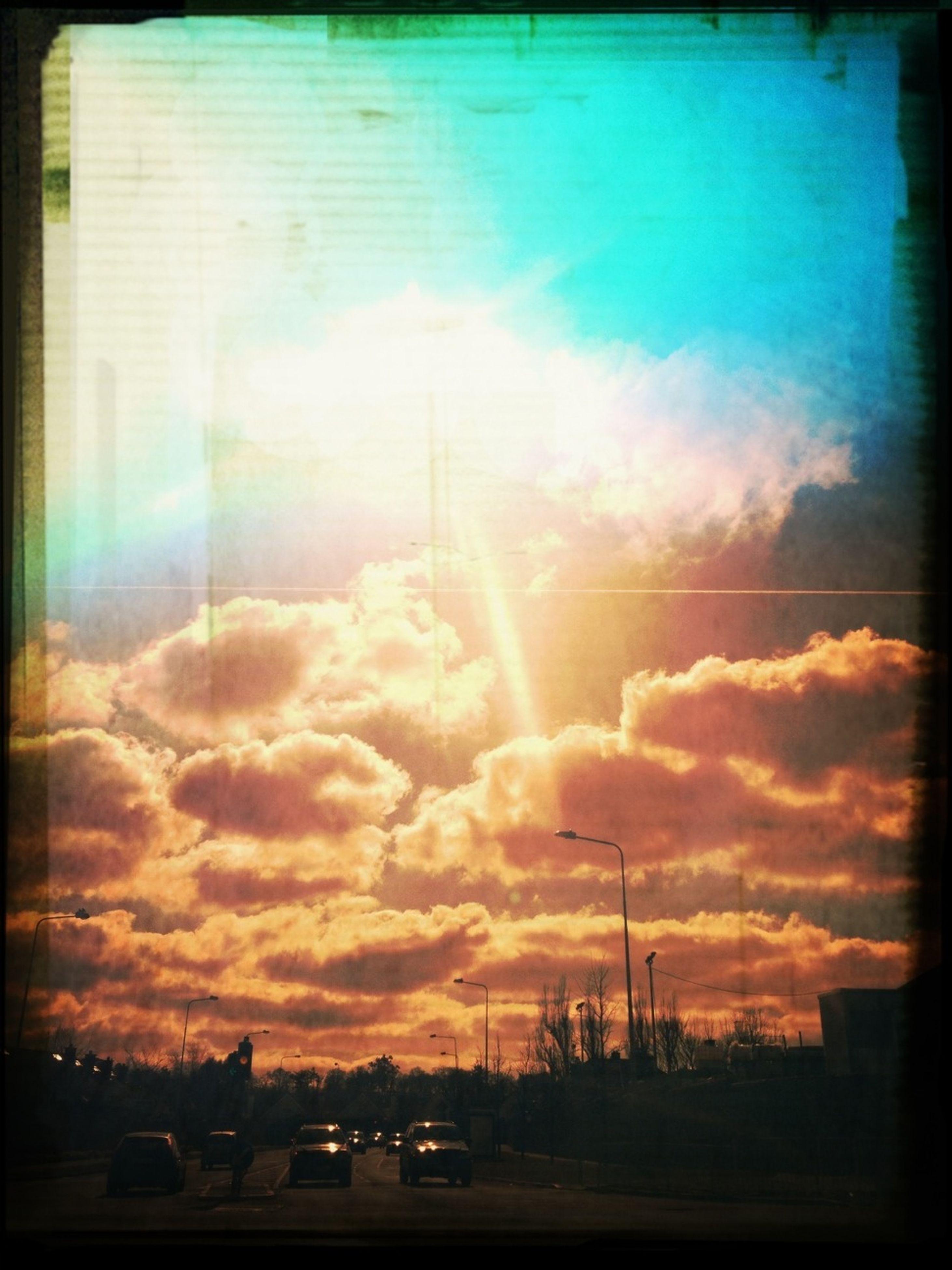sunset, transportation, sky, car, silhouette, transfer print, mode of transport, cloud - sky, land vehicle, auto post production filter, dramatic sky, orange color, cloudy, road, cloud, beauty in nature, nature, sun, street light, scenics