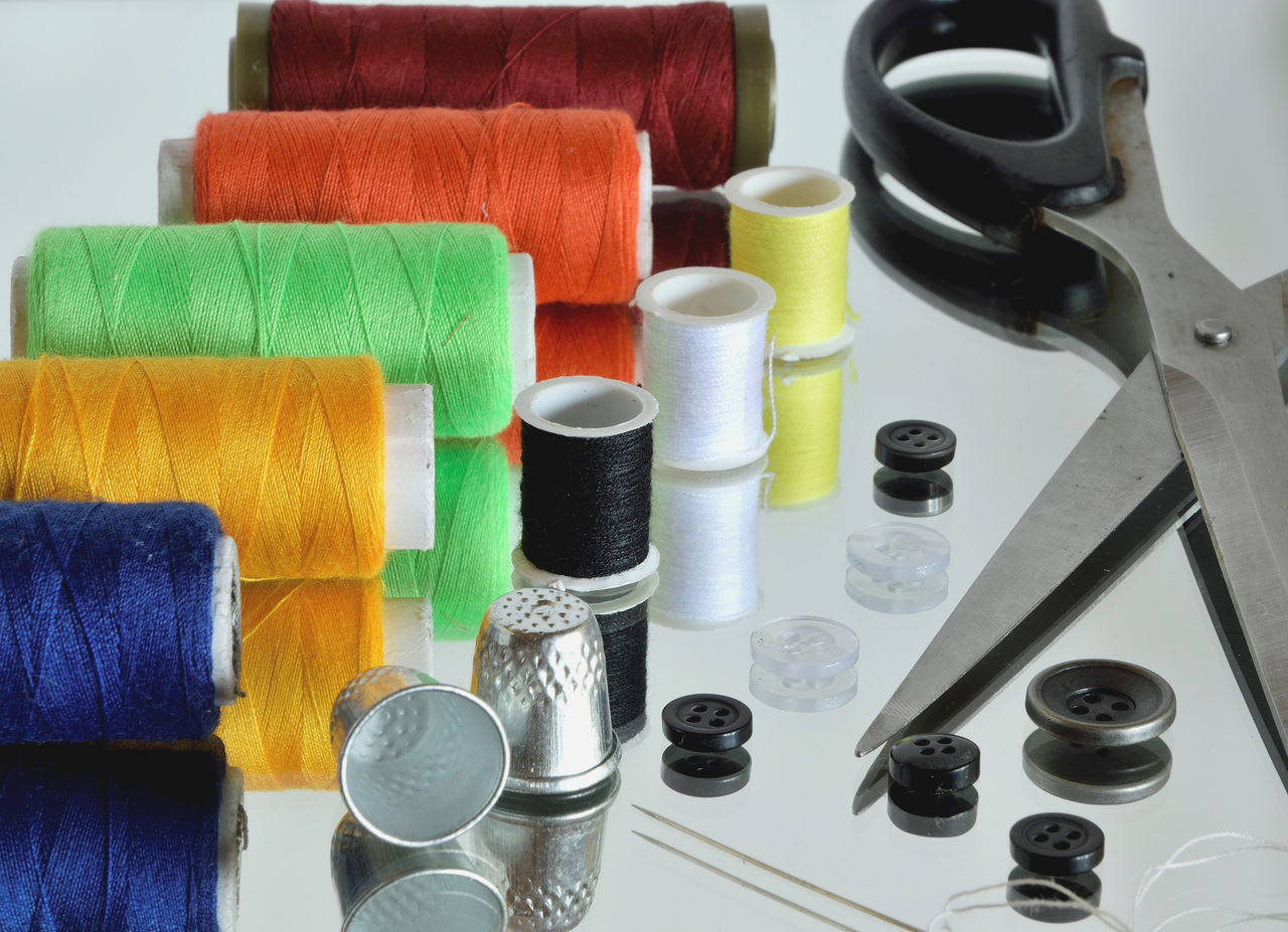 Close-Up Of Sewing Items On Glass Table