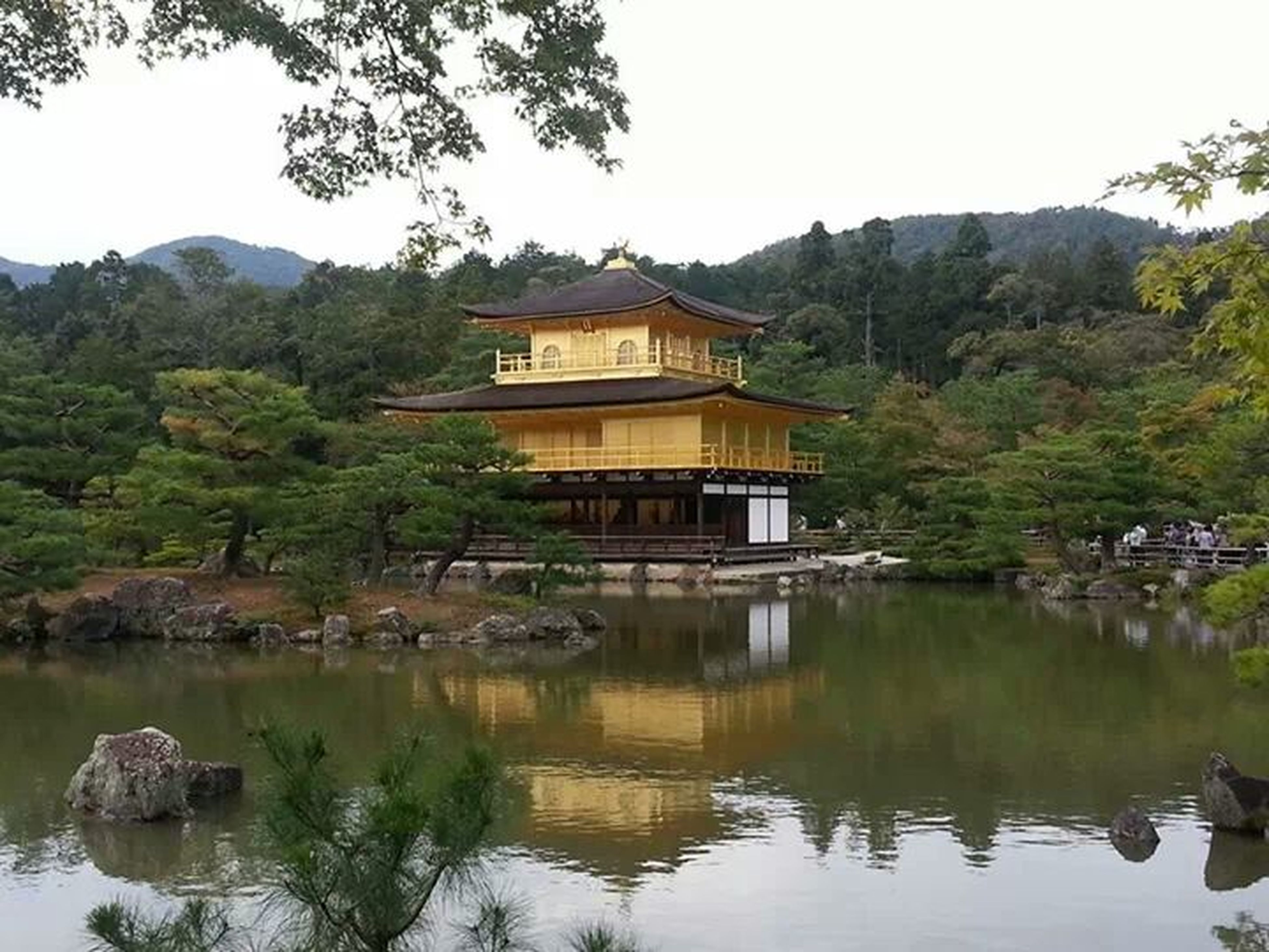 water, tree, built structure, architecture, mountain, reflection, building exterior, lake, waterfront, clear sky, house, tranquility, river, tranquil scene, nature, beauty in nature, scenics, day, mountain range, outdoors
