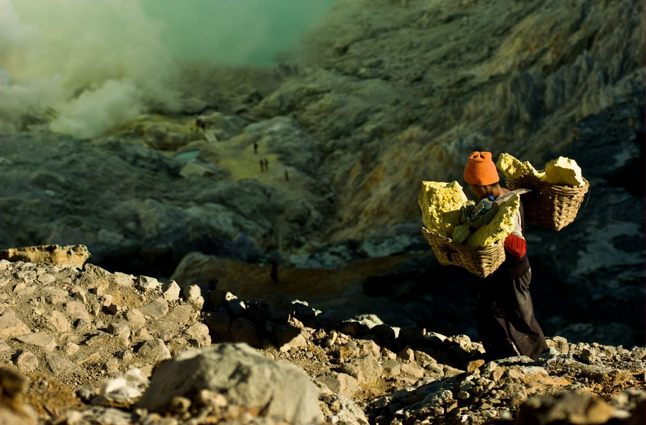 Worker Carrying Sulphur While Walking On Rocky Mountain