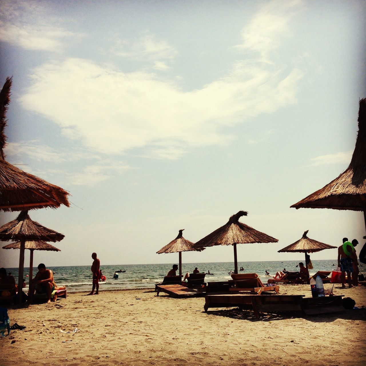 beach, sea, water, beach umbrella, sand, horizon over water, nature, beauty in nature, shore, vacations, sky, tranquility, scenics, tranquil scene, outdoors, cloud - sky, thatched roof, day, summer, real people, men, lifestyles, one person, people