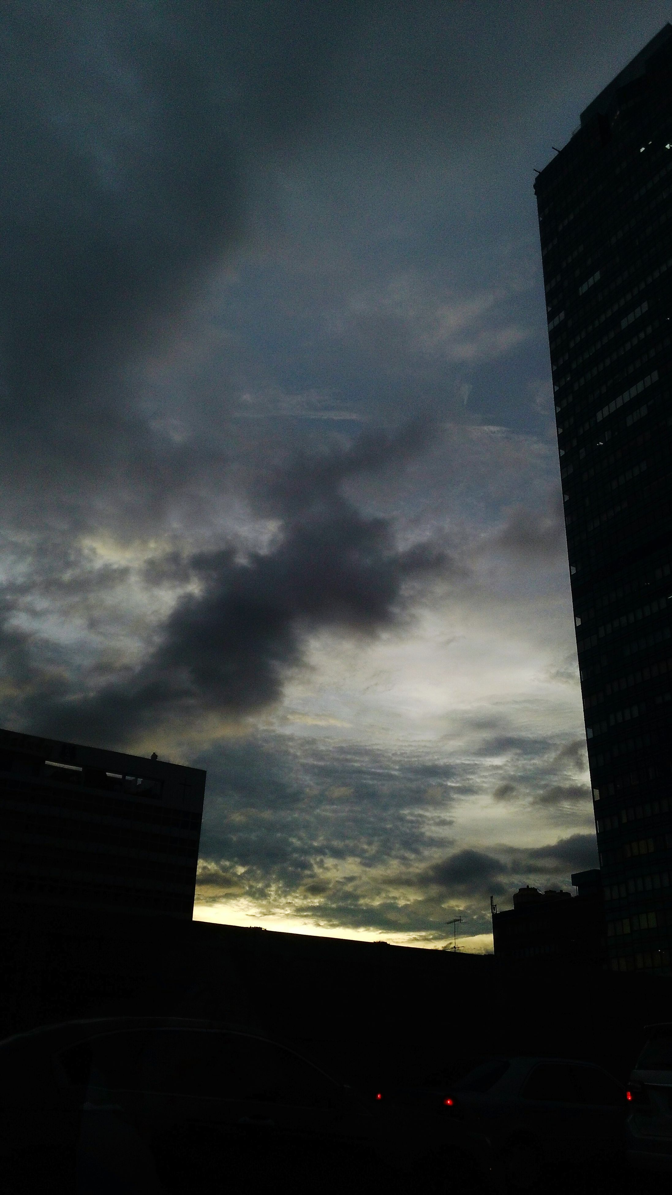building exterior, architecture, built structure, city, sky, cloud - sky, low angle view, skyscraper, building, silhouette, cloudy, office building, tall - high, dusk, city life, sunset, modern, cloud, residential building, tower