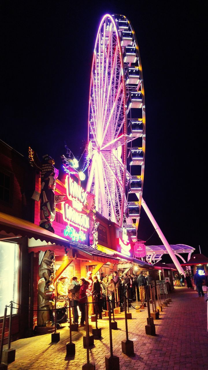 night, arts culture and entertainment, illuminated, amusement park, leisure activity, large group of people, built structure, clear sky, low angle view, real people, amusement park ride, architecture, lifestyles, men, building exterior, ferris wheel, outdoors, women, neon, sky, city, people