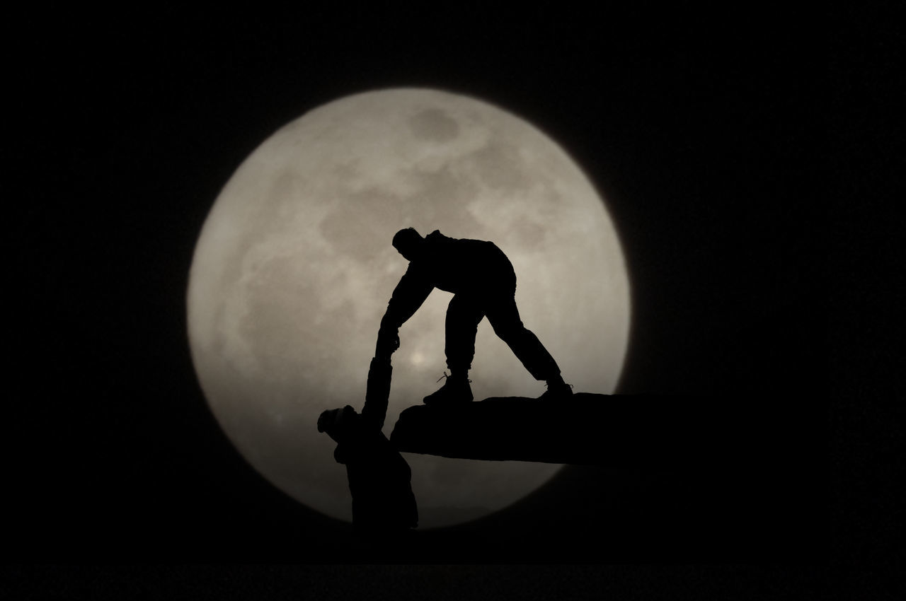 Silhouette Person Helping Friend To Climb On Rock Against Moon At Night