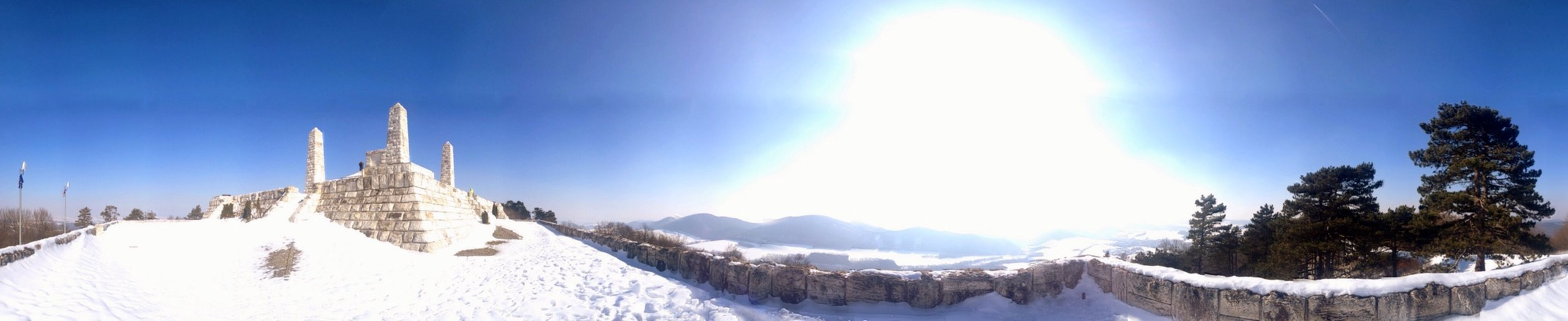 blue, built structure, architecture, religion, sunlight, building exterior, water, sky, tranquility, place of worship, spirituality, tranquil scene, snow, sun, scenics, clear sky, nature, mountain, cold temperature, lake