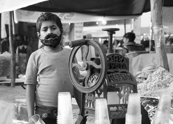 A young kid posing as a grown up man, mans a juice stalls at the annual Lucknow Mahotsav festival.Streetphotography World Photography Day Black And White Portrait Young Boy Portrait Of A Man  Portrait Of A Child Manchild Environmental Portraits Learn & Shoot: Working To A Brief Youth Of Today Telling Stories Differently Up Close Street Photography My Favorite Photo Street Photography The Street Photographer - 2016 EyeEm Awards The Portraitist - 2016 EyeEm Awards The Photojournalist - 2016 EyeEm Awards Found On The Roll TakeoverContrast Monochrome Photography
