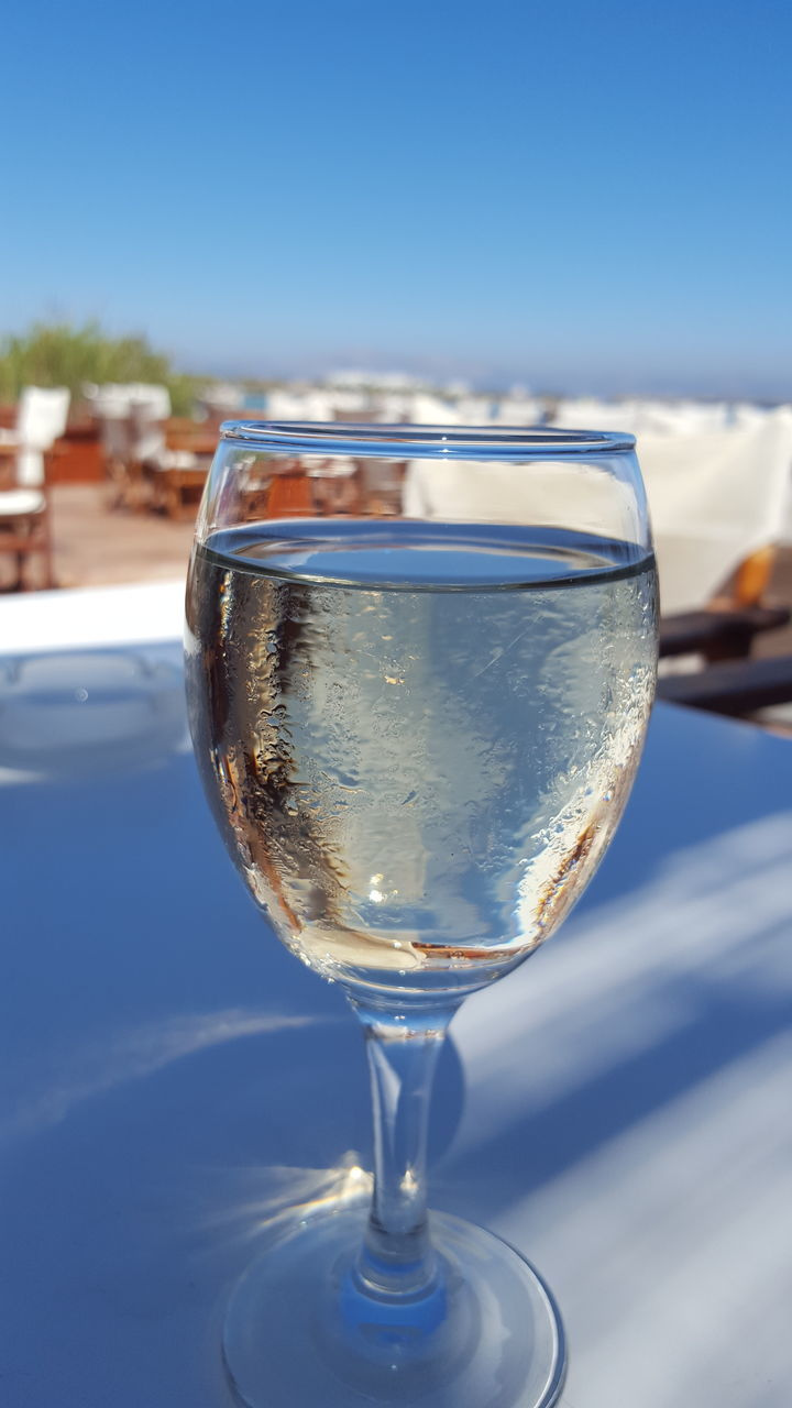 drink, focus on foreground, sky, close-up, alcohol, drinking glass, food and drink, outdoors, blue, no people, refreshment, day, wineglass, freshness