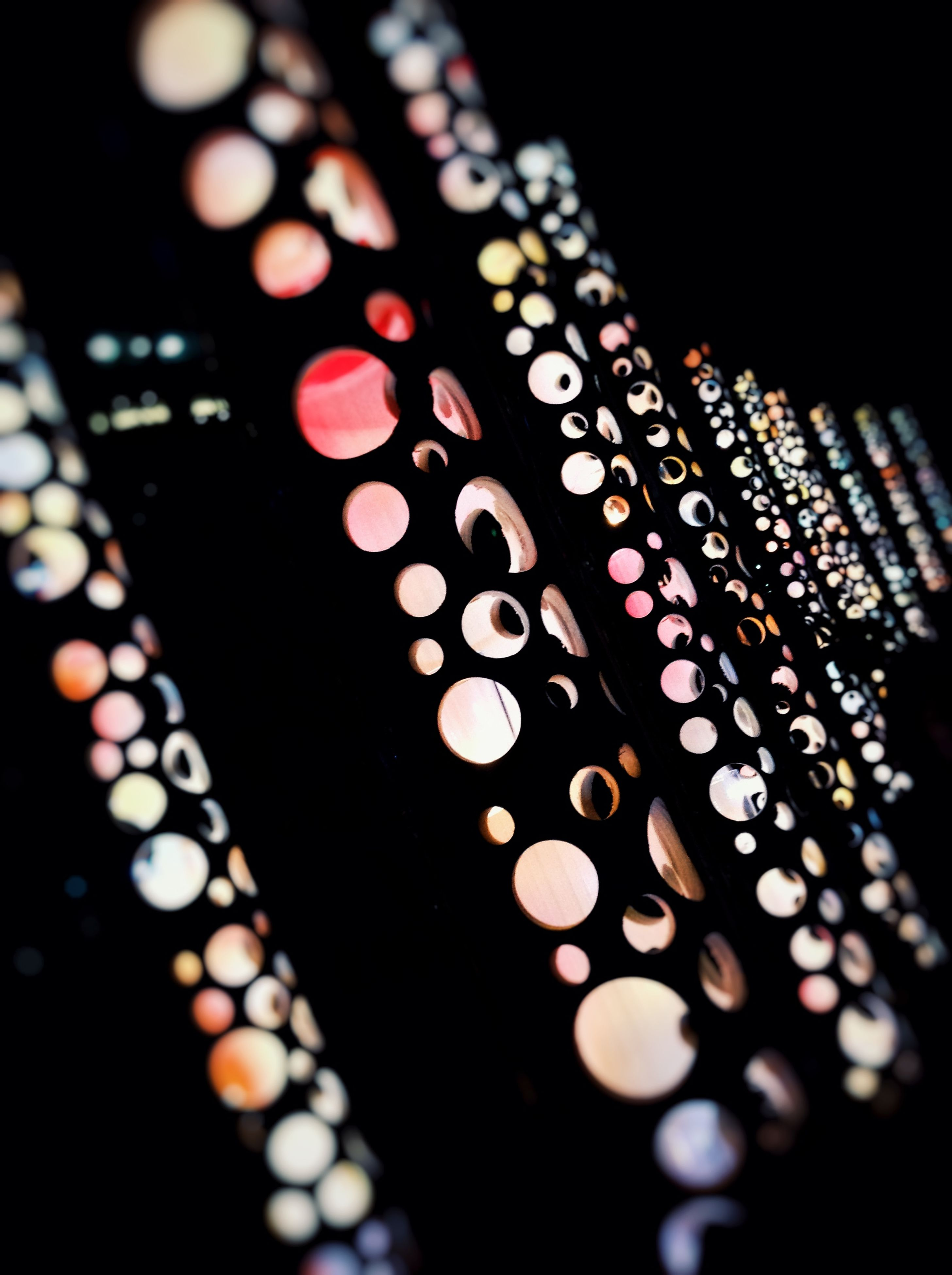 indoors, close-up, illuminated, pattern, selective focus, night, design, still life, decoration, in a row, no people, focus on foreground, arts culture and entertainment, lighting equipment, part of, large group of objects, glowing, art and craft, light - natural phenomenon, black background