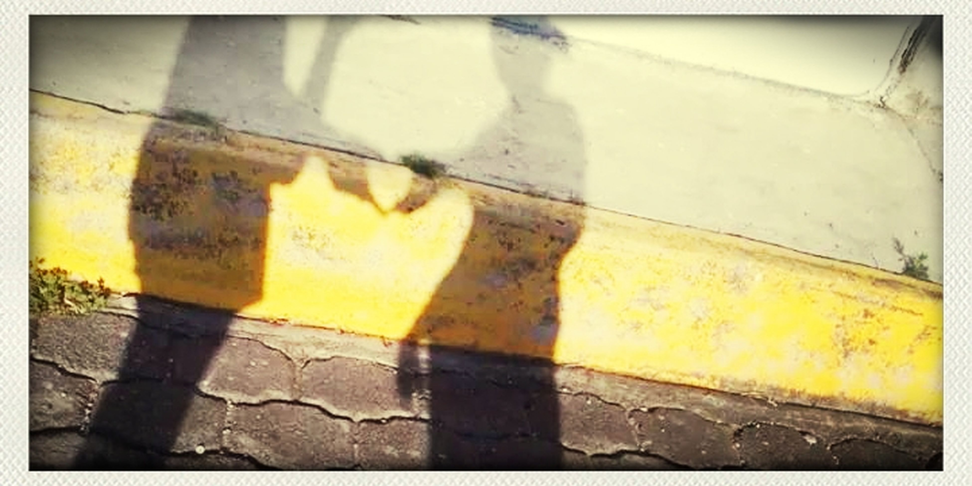 transfer print, auto post production filter, street, cobblestone, sidewalk, yellow, outdoors, sunlight, paving stone, high angle view, day, transportation, no people, footpath, shadow, built structure, wall - building feature, close-up, tiled floor, wet