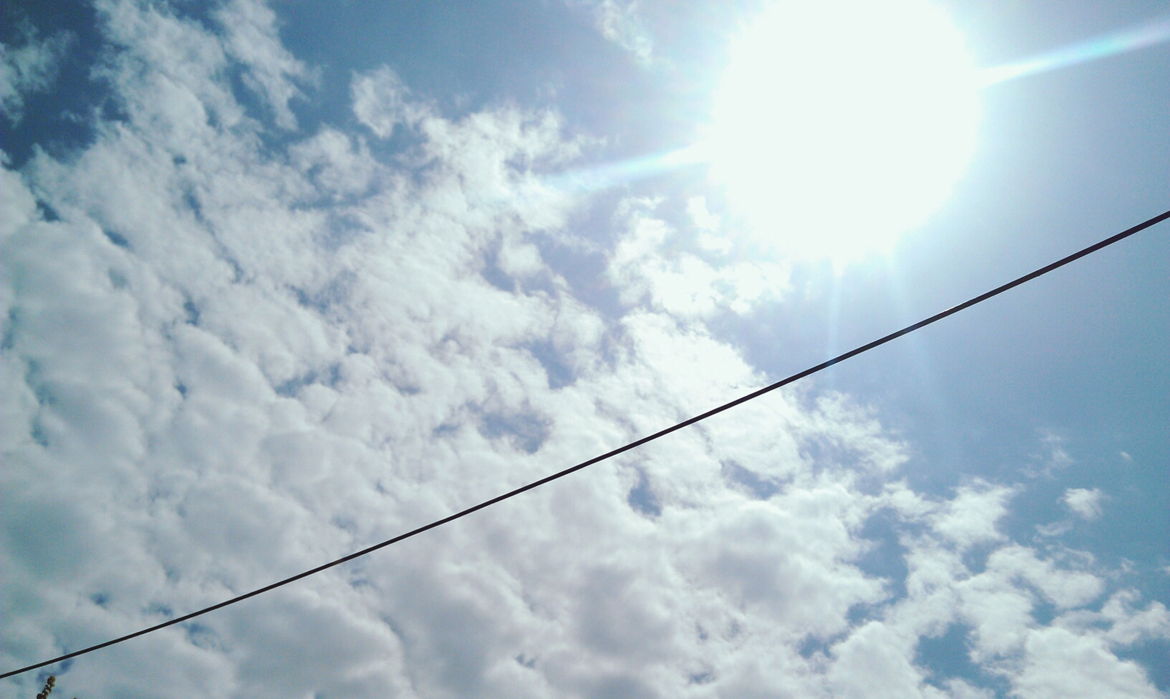 low angle view, sky, cloud - sky, power line, cloudy, cable, cloud, sun, electricity, nature, blue, tranquility, beauty in nature, sunlight, sunbeam, power supply, outdoors, day, connection, no people