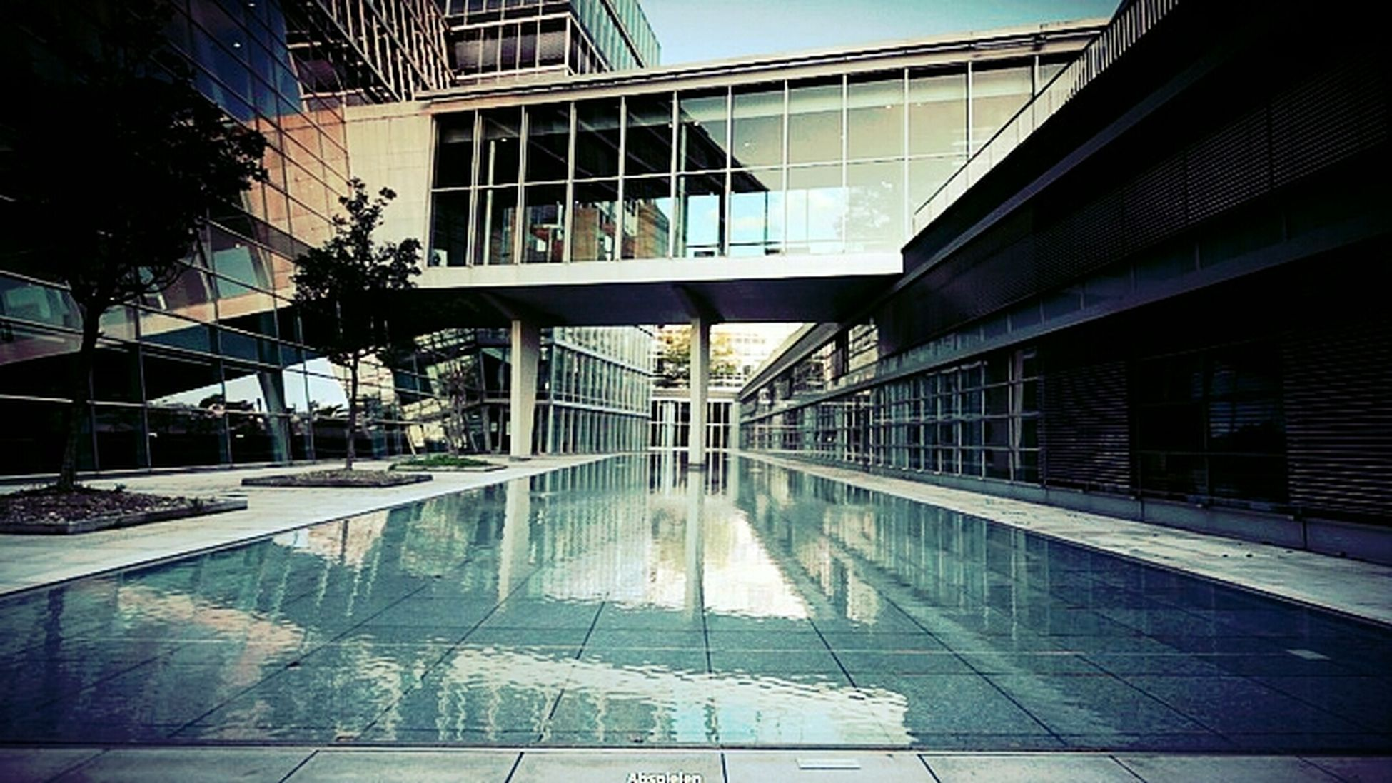 building exterior, architecture, built structure, reflection, building, city, glass - material, modern, window, office building, residential building, low angle view, water, residential structure, day, sunlight, outdoors, railing, no people, glass