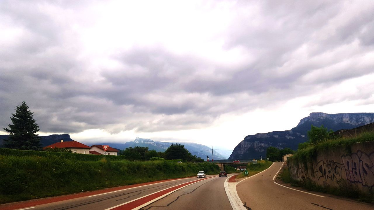 road, the way forward, transportation, road marking, cloud - sky, sky, mountain, nature, street, outdoors, landscape, tranquility, dividing line, scenics, day, curve, no people, tree, storm cloud, beauty in nature, winding road