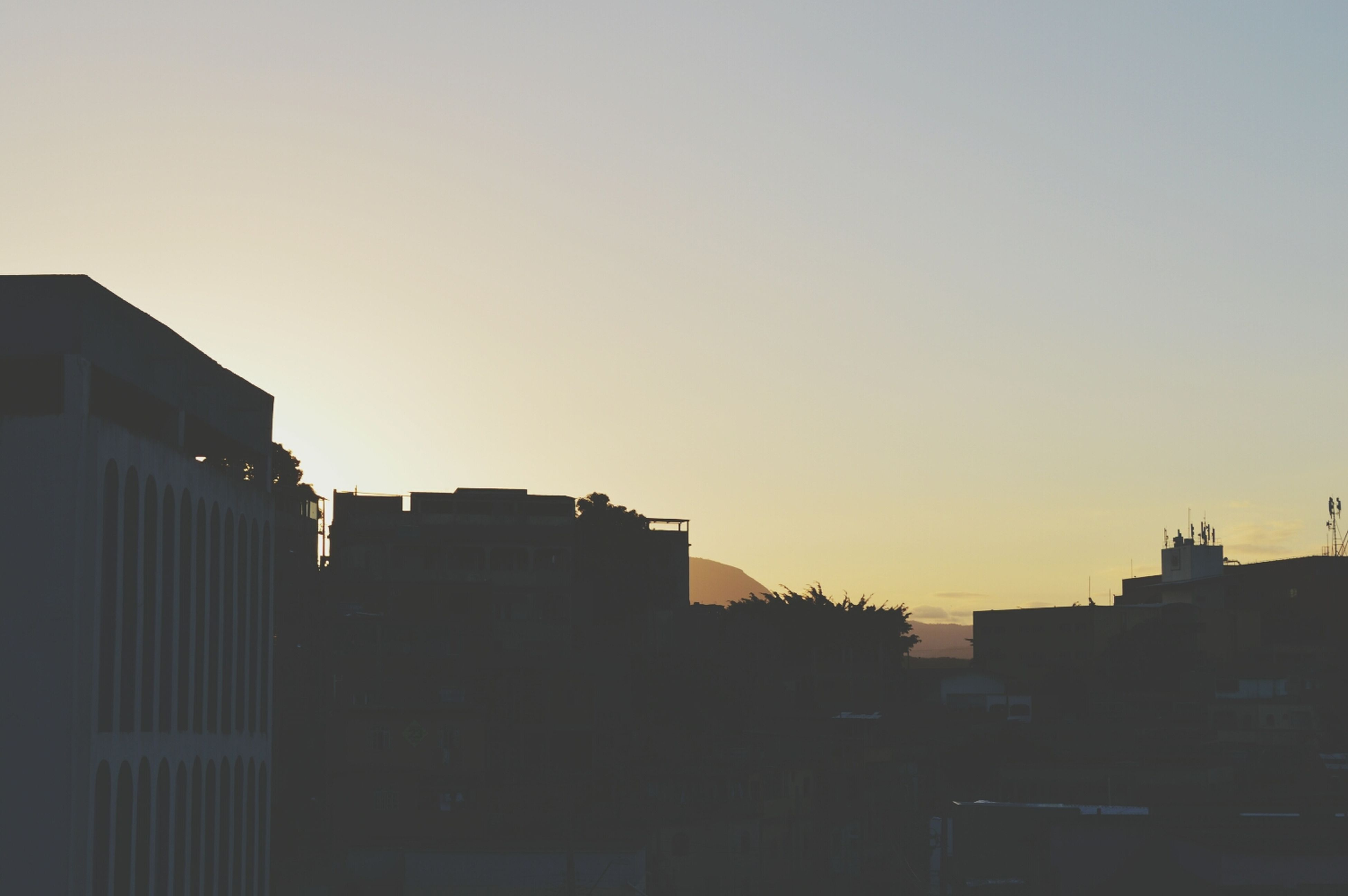 building exterior, architecture, built structure, clear sky, copy space, city, sunset, residential building, residential structure, building, low angle view, residential district, outdoors, house, silhouette, no people, city life, orange color, sky, dusk