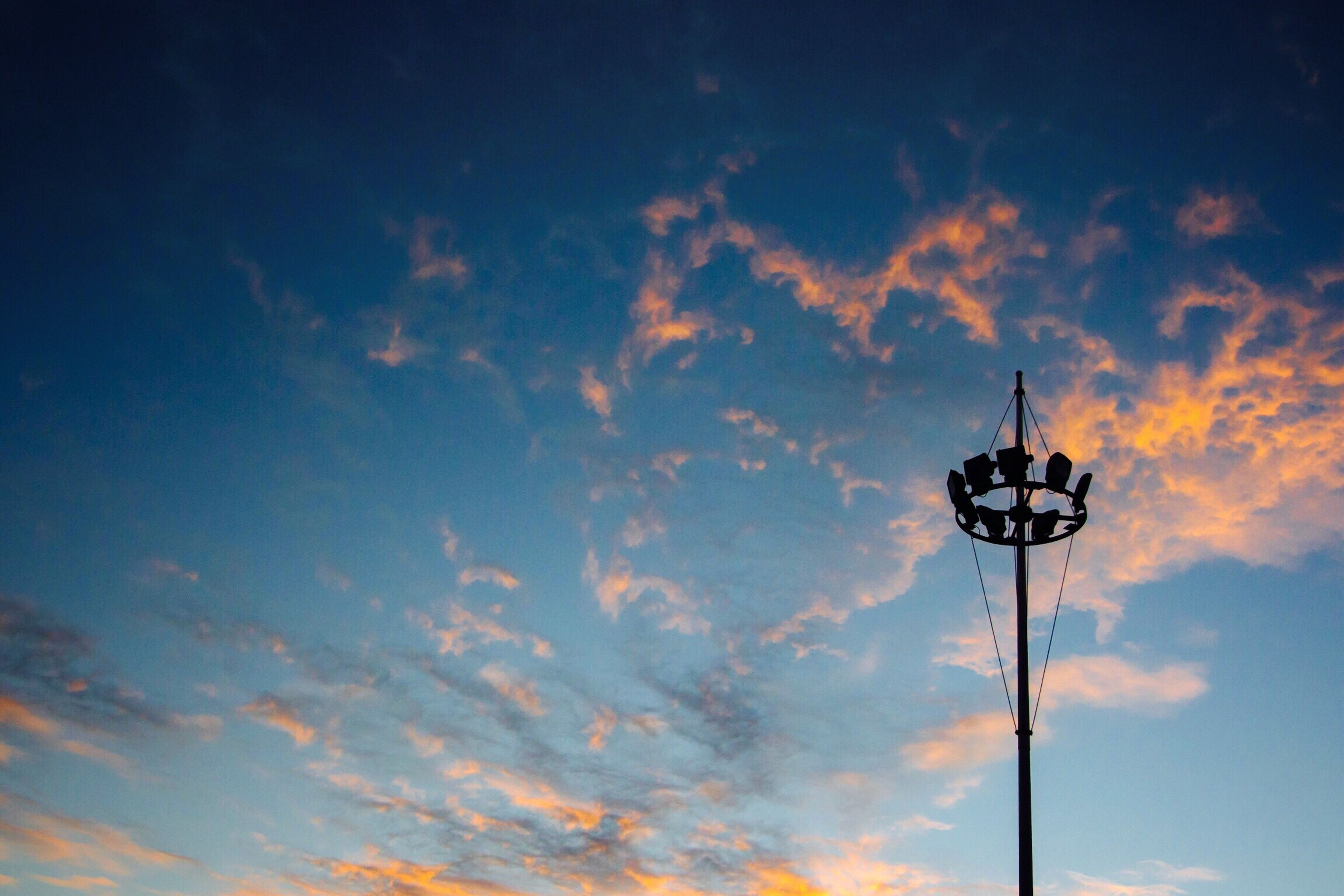 low angle view, sky, street light, cloud - sky, lighting equipment, blue, sunset, cloudy, cloud, silhouette, nature, pole, electricity, outdoors, no people, beauty in nature, technology, tranquility, dusk, orange color