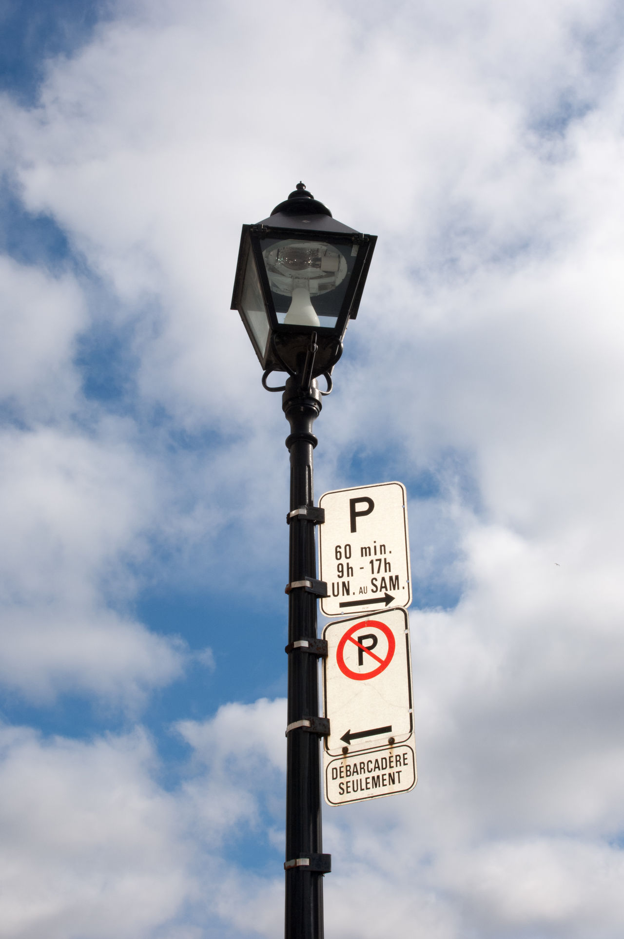 Black lamp post with blue skies and puffy clouds with no parking signs and days, hours of permitted parking times in French. Montreal, Quebec, Canada. Day Lamp Lamp Post Lamplight Lamppost Low Angle View No Parking No Parking Sign No Parking Signs No People Outdoors Sky Text
