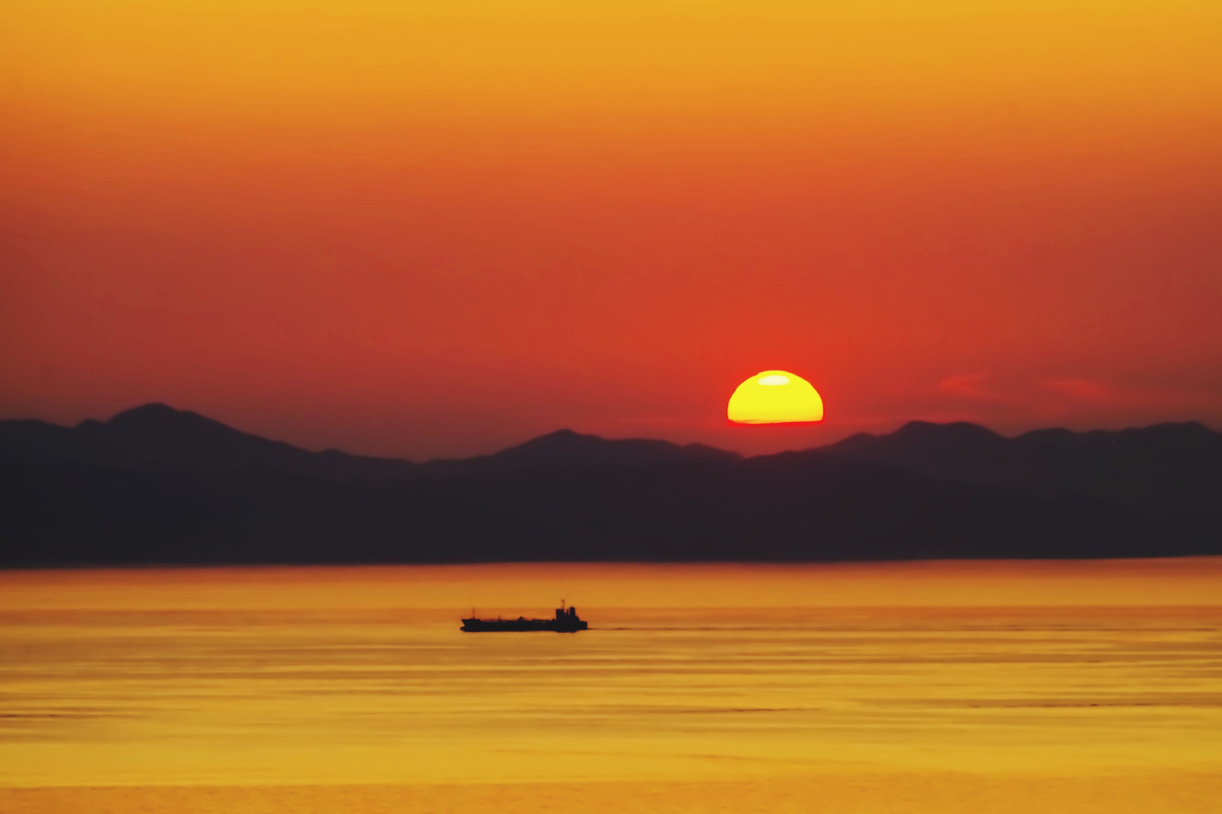 sunset, orange color, nature, beauty in nature, silhouette, scenics, tranquility, boat, sky, nautical vessel, transportation, water, mode of transport, mountain, tranquil scene, sun, no people, outdoors, waterfront, sea, mountain range, clear sky, day