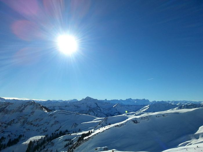 Sun over the Austrian Alps in winter Alps Austrian Alps Beauty In Nature Blue Cold Temperature Horizontal Landscape Lens Flare Mountain Mountain Range Mountain View Mountains Nature Outdoors Panorama Scenics Skiing Sky Snow Snowcapped Mountain Sun Sunbeam Sunlight Tranquility Winter