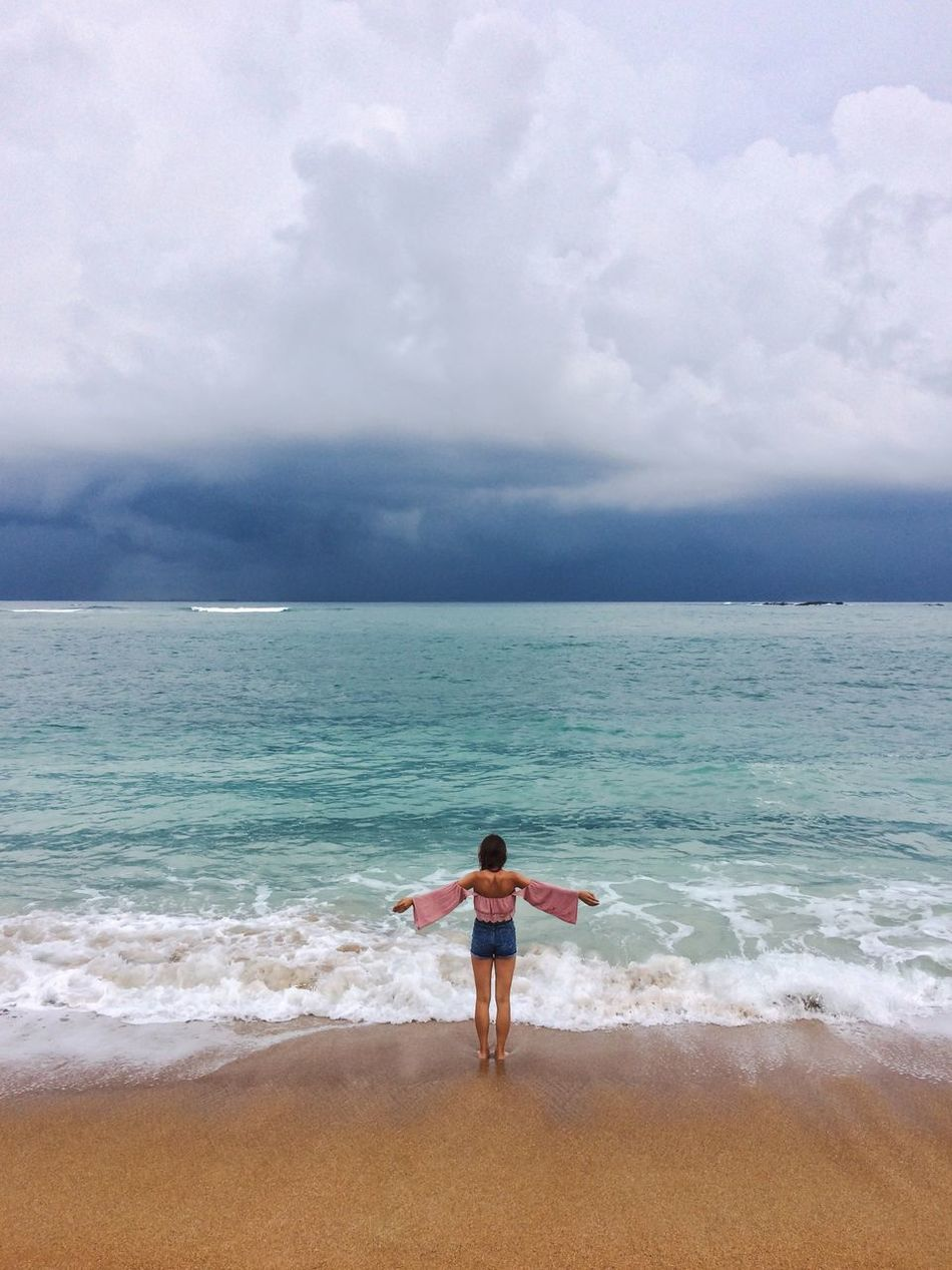 A rear view of a woman standing on a shore with the arms wide spread, in a stormy weather. Beach Beauty In Nature Colors Of Life Cloud - Sky Cloudy Coastline Full Length Horizon Over Water Idyllic Leisure Activity Lifestyles Nature Outdoors Scenics Sea Shore Sky Stormy Weather Color Palette Tranquil Scene Tranquility Unawatuna Vacations Water Wave