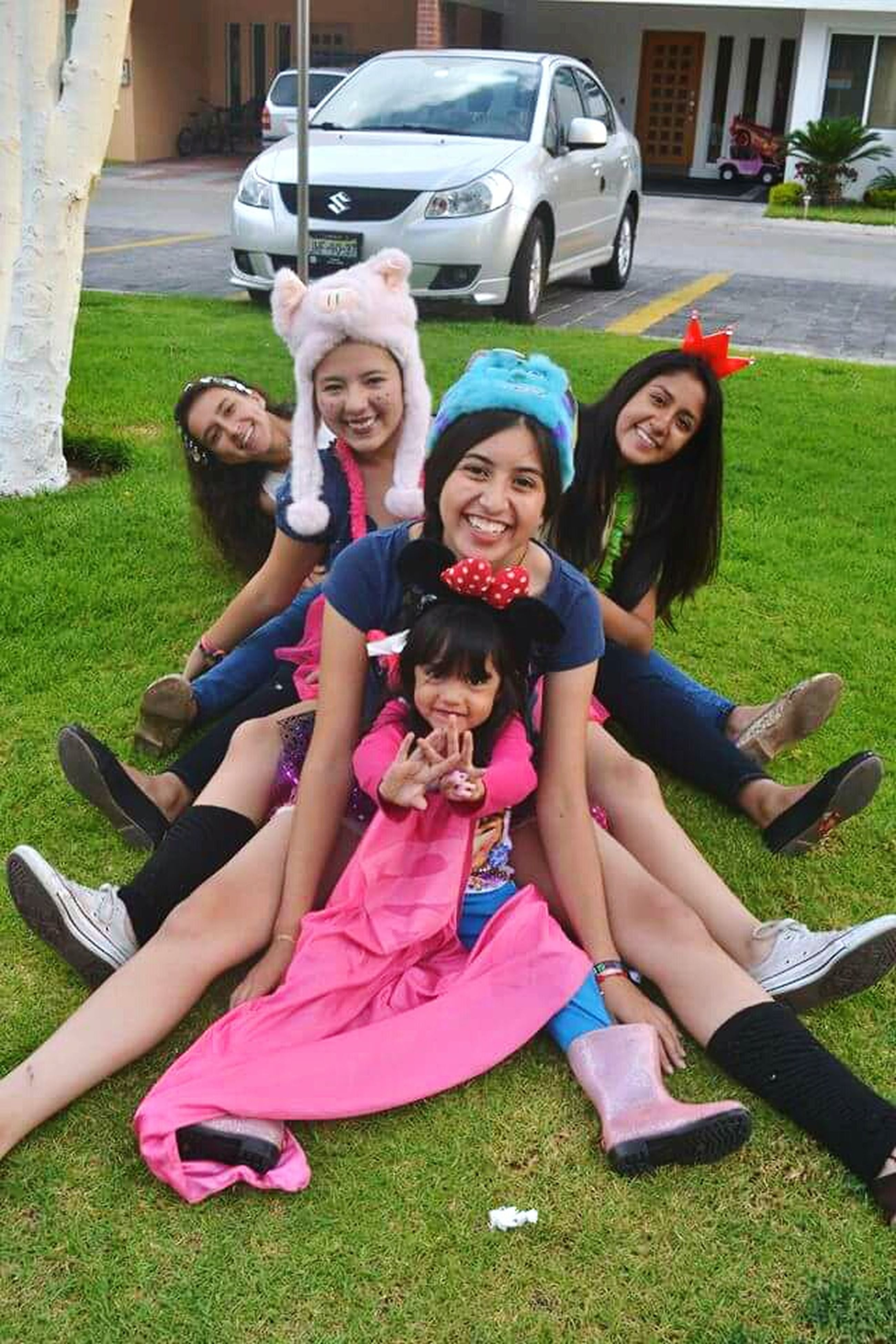person, lifestyles, leisure activity, grass, childhood, casual clothing, happiness, elementary age, sitting, full length, fun, smiling, girls, park - man made space, togetherness, enjoyment, looking at camera, playing