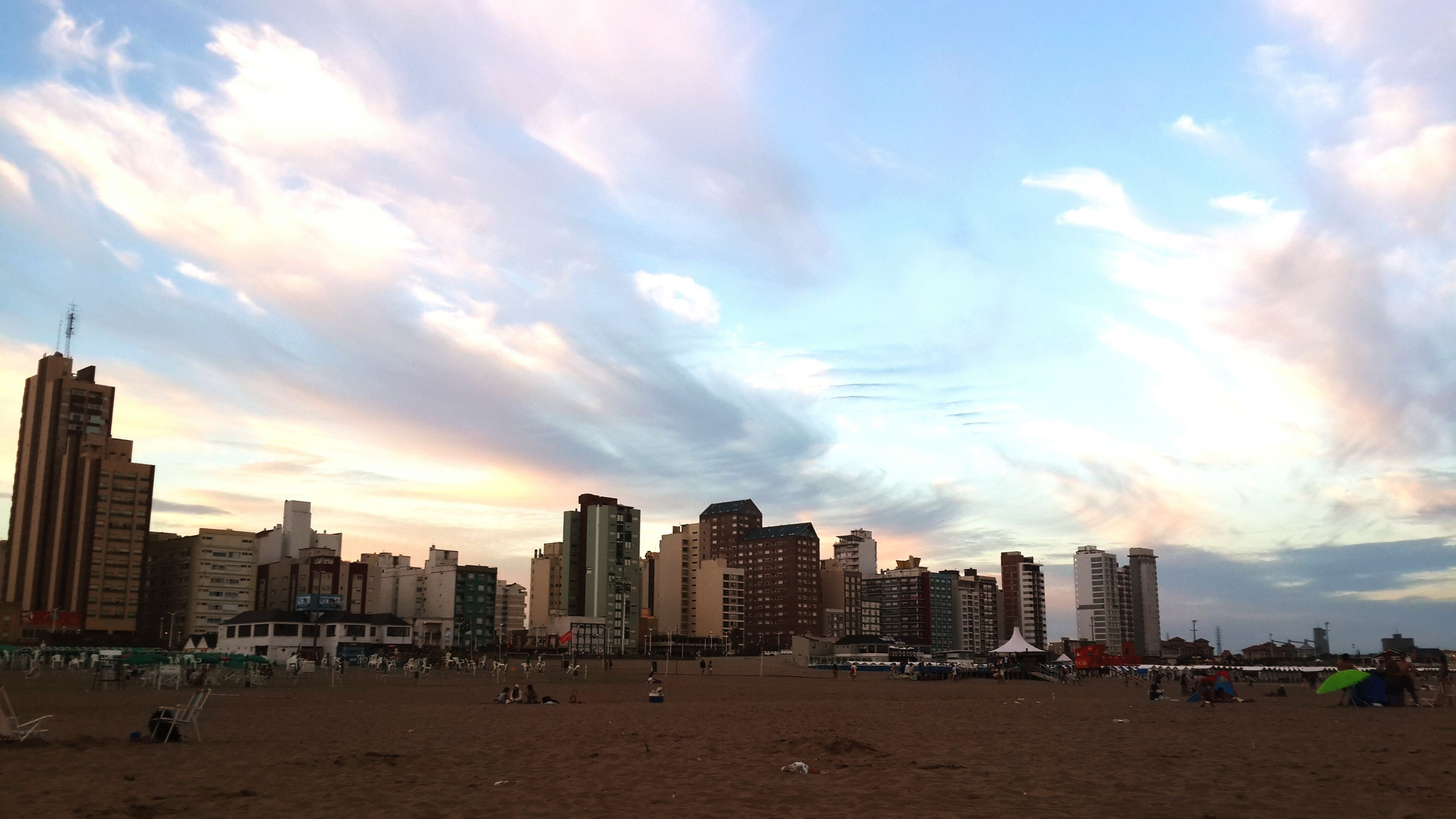 building exterior, architecture, city, built structure, sky, cloud - sky, skyscraper, cityscape, beach, city life, urban skyline, modern, tall - high, large group of people, cloud, office building, tower, cloudy, sand