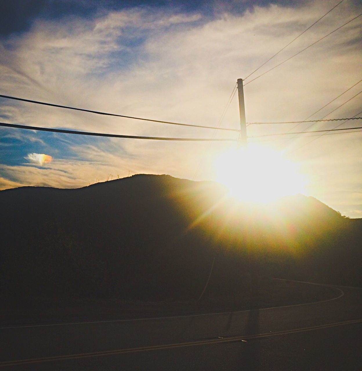 cable, sun, sky, sunbeam, lens flare, sunlight, power line, connection, electricity, nature, sunset, no people, scenics, power supply, tranquility, beauty in nature, outdoors, cloud - sky, tranquil scene, silhouette, landscape, electricity pylon, low angle view, day, mountain, vapor trail