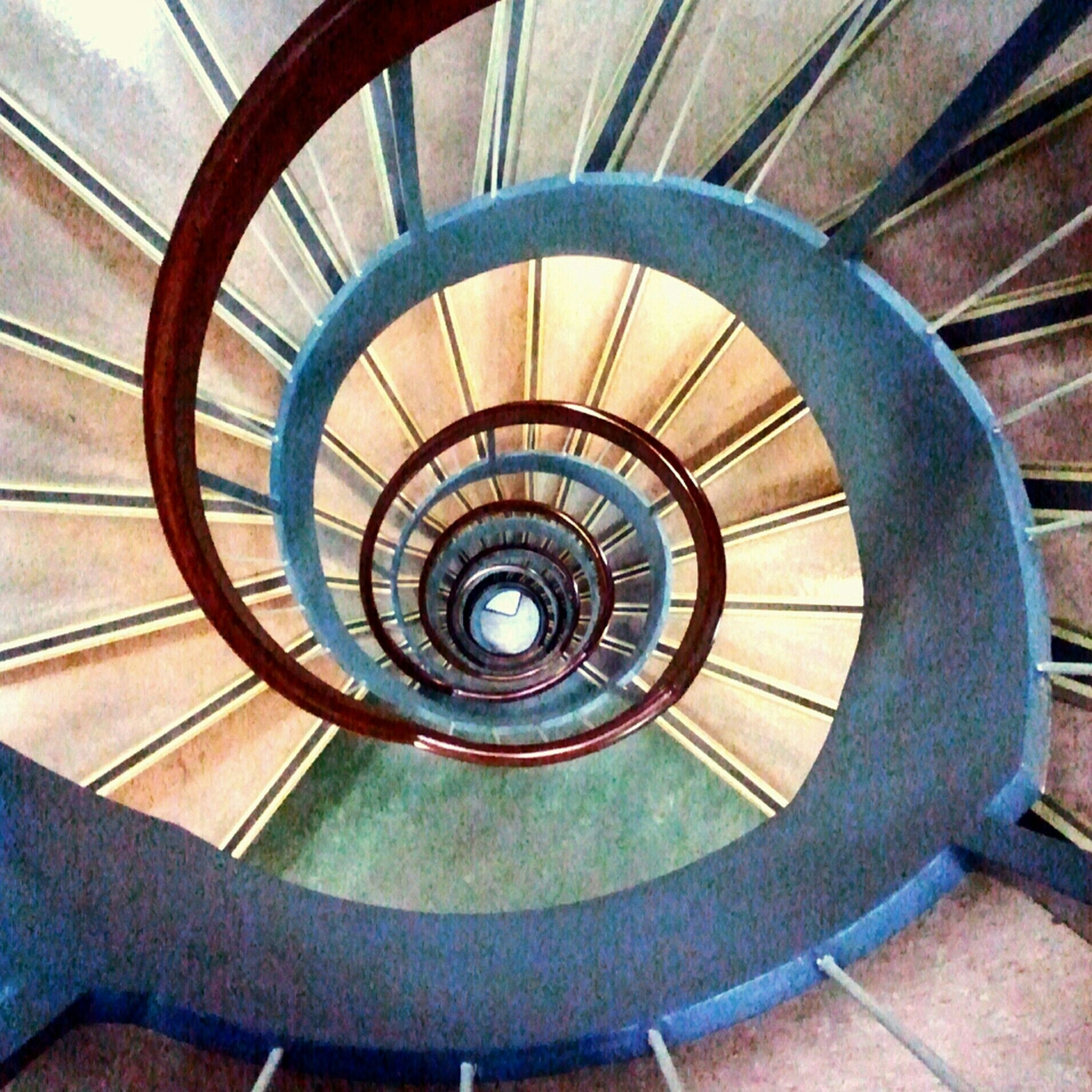indoors, steps and staircases, spiral staircase, steps, staircase, spiral, railing, architecture, built structure, pattern, circle, ceiling, directly below, high angle view, stairs, geometric shape, design, modern, directly above, building