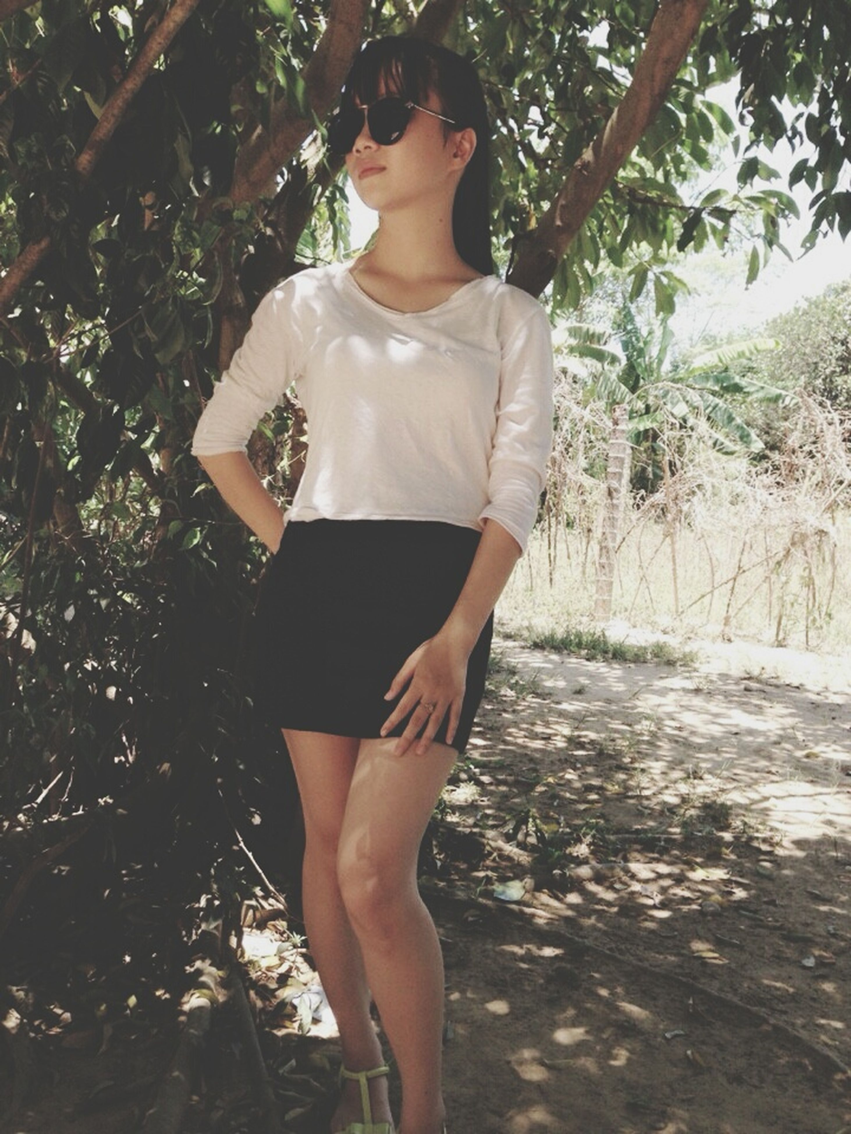 tree, young adult, lifestyles, young women, leisure activity, standing, front view, person, casual clothing, sunlight, full length, sensuality, day, dress, tree trunk, outdoors