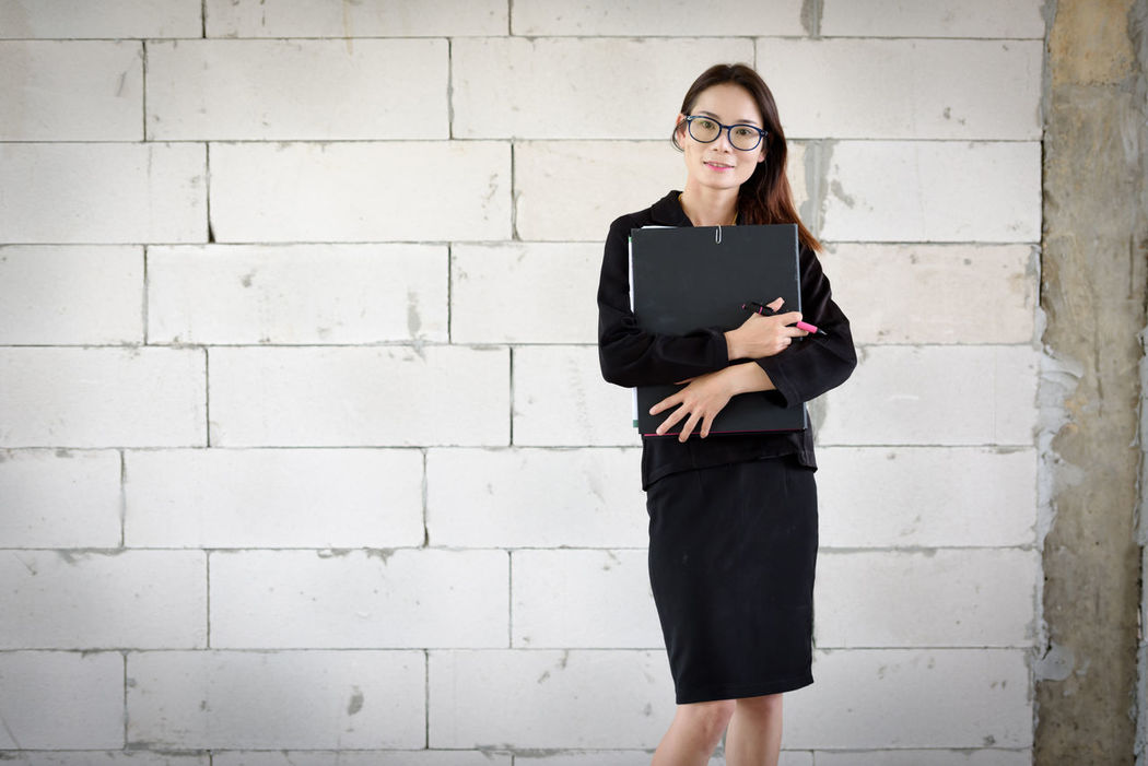Businesswoman standing holding a file in a brick building. Beautiful Woman Beauty Business Businesswoman Cheerful Confidence  Corporate Business Day Eyeglasses  Eyewear Happiness Holding Indoors  Long Hair Looking At Camera One Person One Woman Only Portrait Real People Smiling Standing Wall - Building Feature Women Young Adult Young Women
