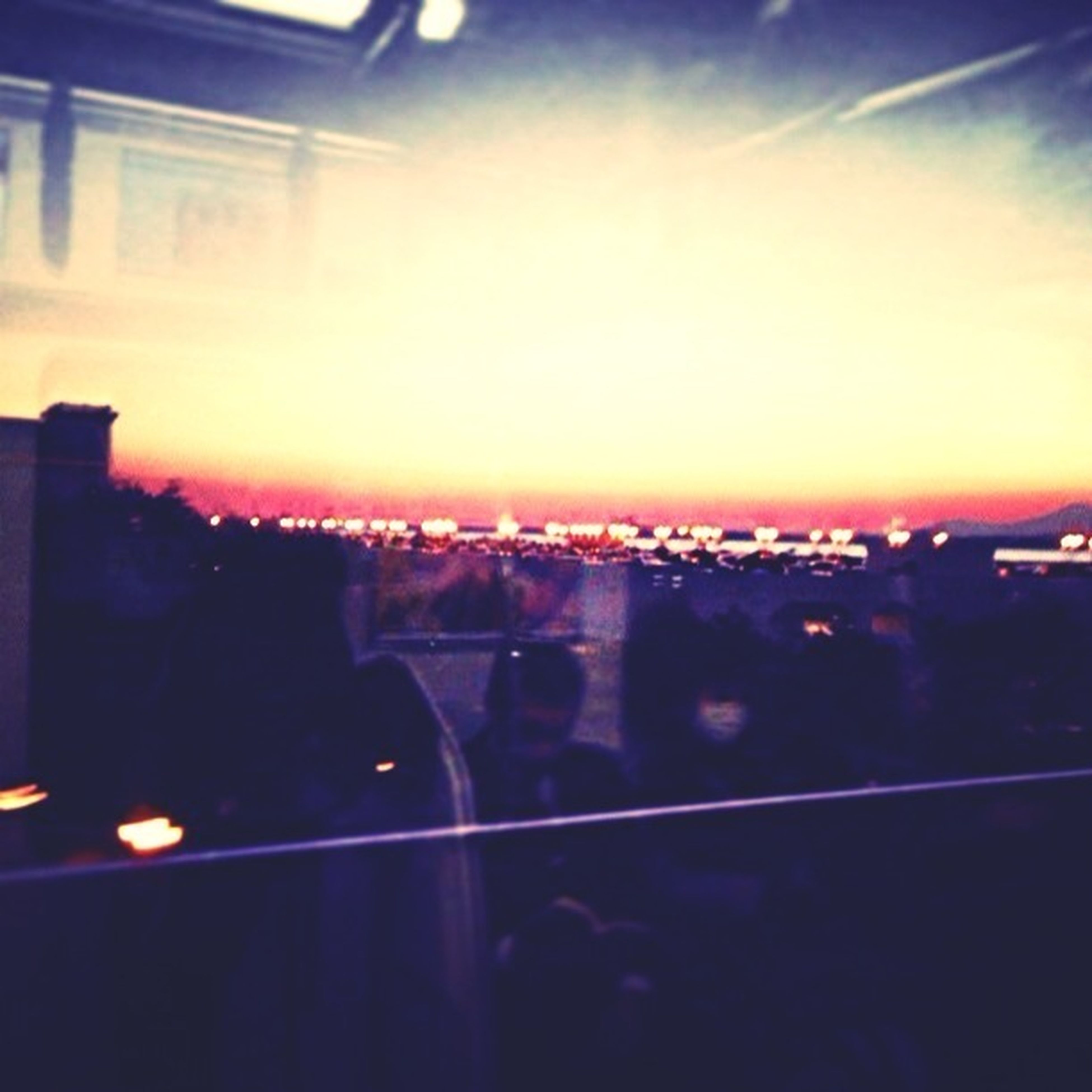 illuminated, sunset, city, building exterior, architecture, built structure, silhouette, cityscape, sky, orange color, night, lens flare, sun, city life, dusk, outdoors, no people, light - natural phenomenon, transportation