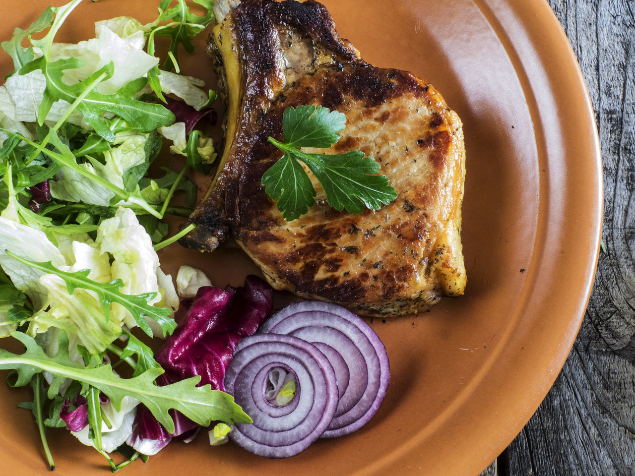 Roasted pork chop on a plate with a green salad, red onion on an old wooden weathered table Broccoli Chop Close-up Day Food Food And Drink Freshness Green Healthy Eating Leaf No People Old Onion Plate Pork Ready-to-eat Relaxing Roasted Salad Serving Size Table Weathered Wooden