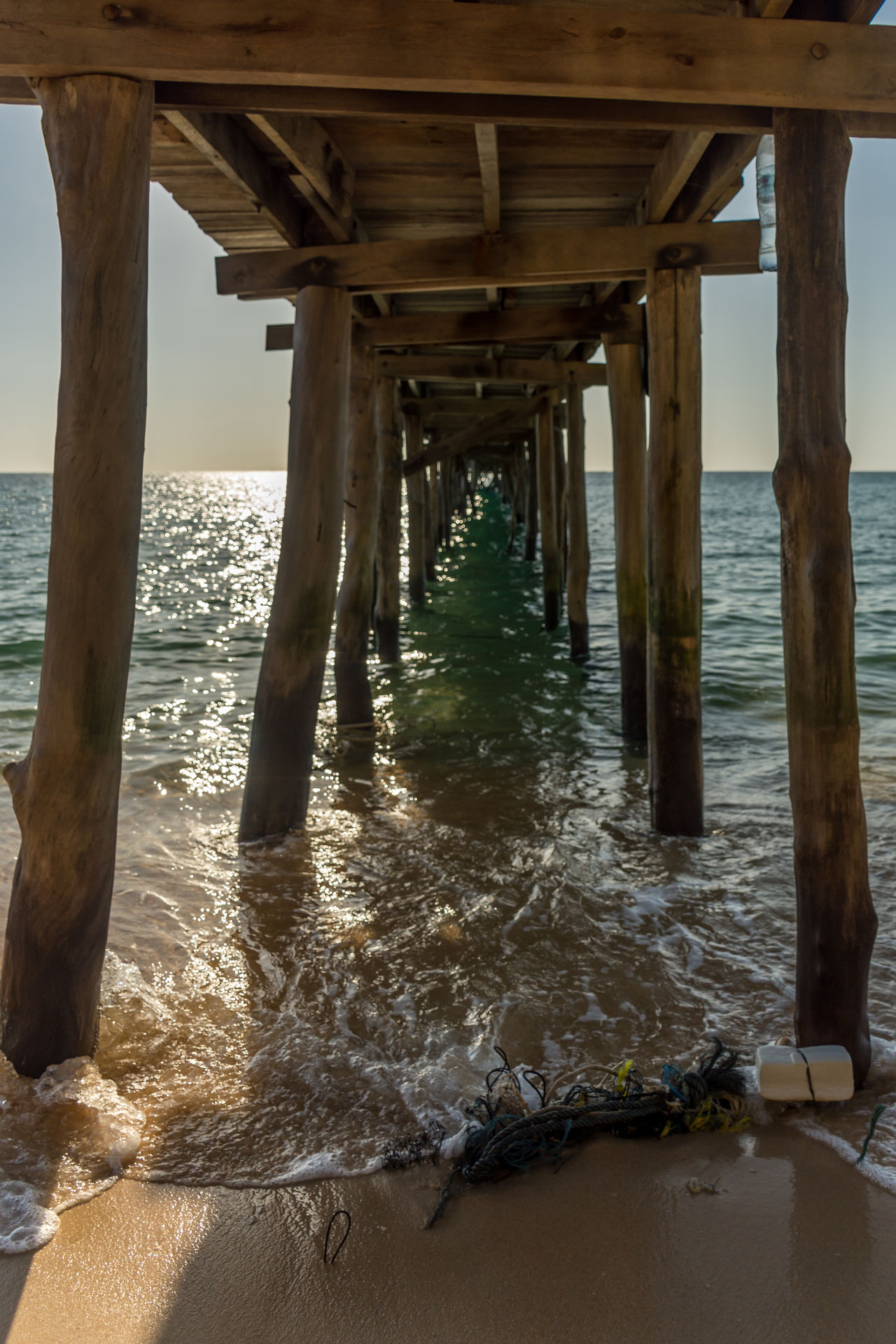 View under a old wooden jetty going out to sea from a golden sand beach. Architectural Column Beach Bridge - Man Made Structure Calm Cambodia Golden Horizon Horizon Over Water Island Jetty Nature Ocean Old Outdoors Pier Posts Rubbish Sand Sea Sun Tide Underneath Waves Wood Wooden