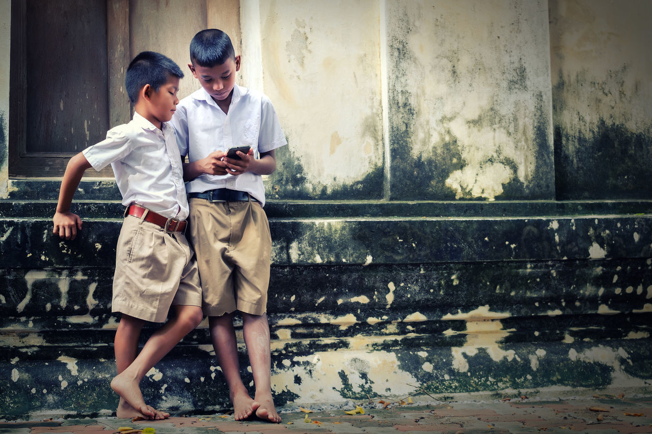 Two asian boys wearing school uniforms are playing game but they are not reading book, old wall temple background Local Thailand Plant Adult Bonding Boys Child Childhood Day Friendship Full Length Indoors  Mobile People Samrtphon Togetherness Two People Young Adult Young Women