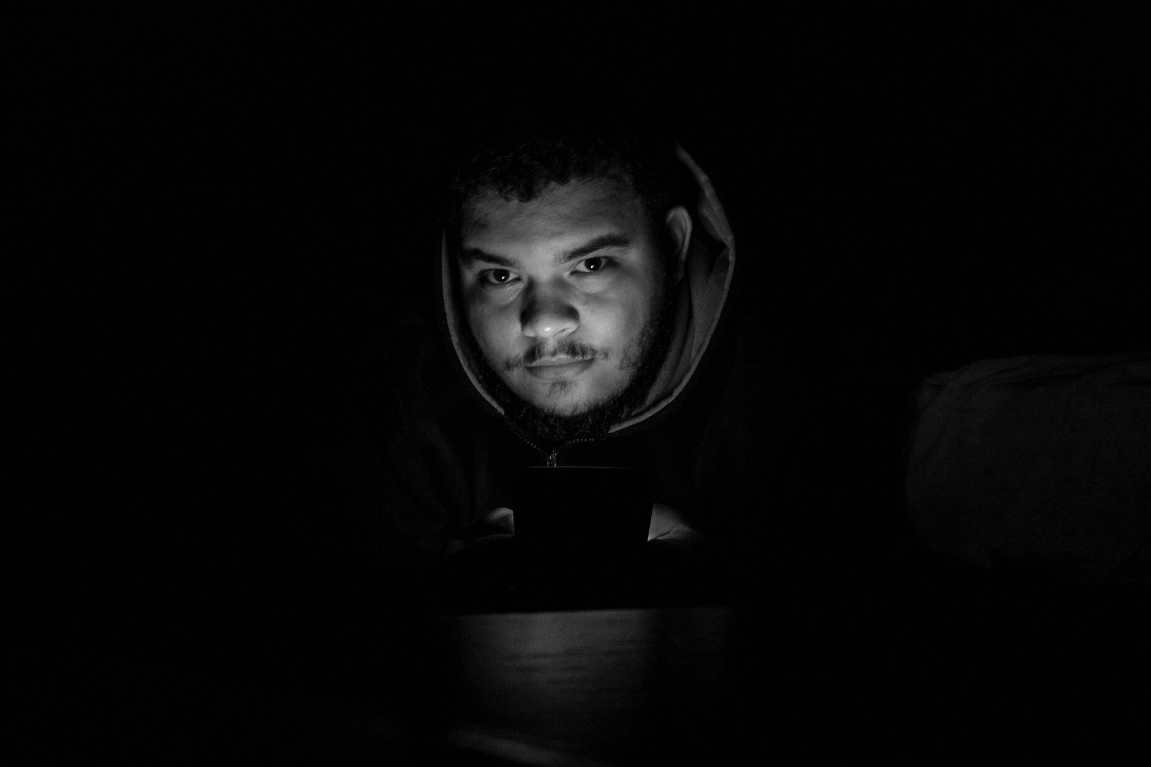indoors, portrait, looking at camera, black background, front view, lifestyles, person, dark, copy space, young adult, studio shot, headshot, leisure activity, darkroom, home interior, casual clothing, contemplation, young men