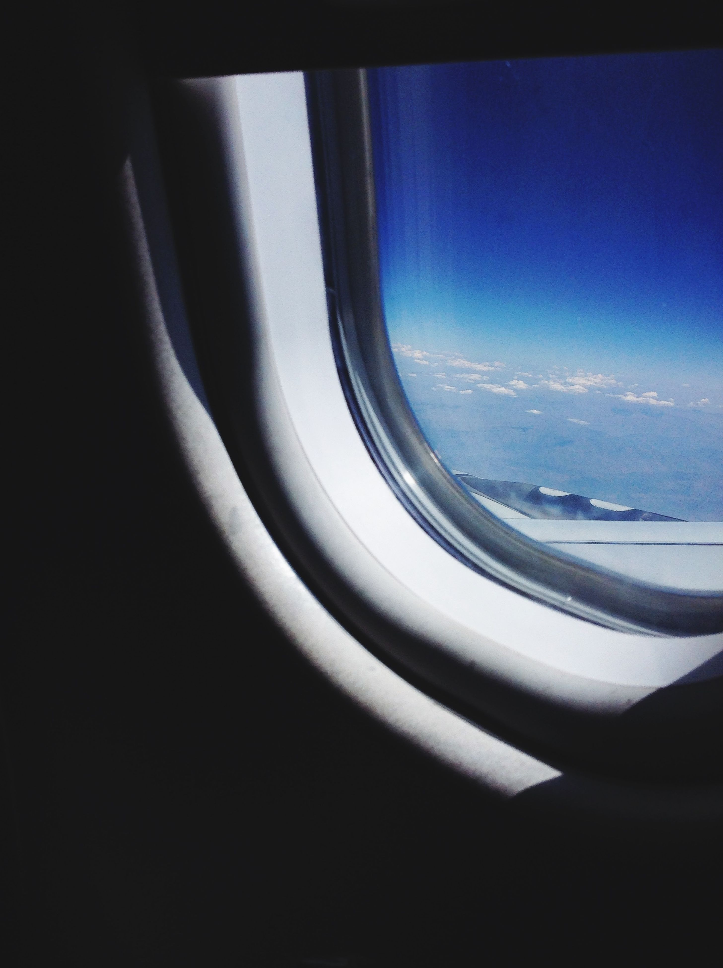 transportation, window, vehicle interior, indoors, airplane, transparent, glass - material, mode of transport, sky, air vehicle, part of, travel, blue, cropped, copy space, clear sky, journey, aerial view, cold temperature, no people