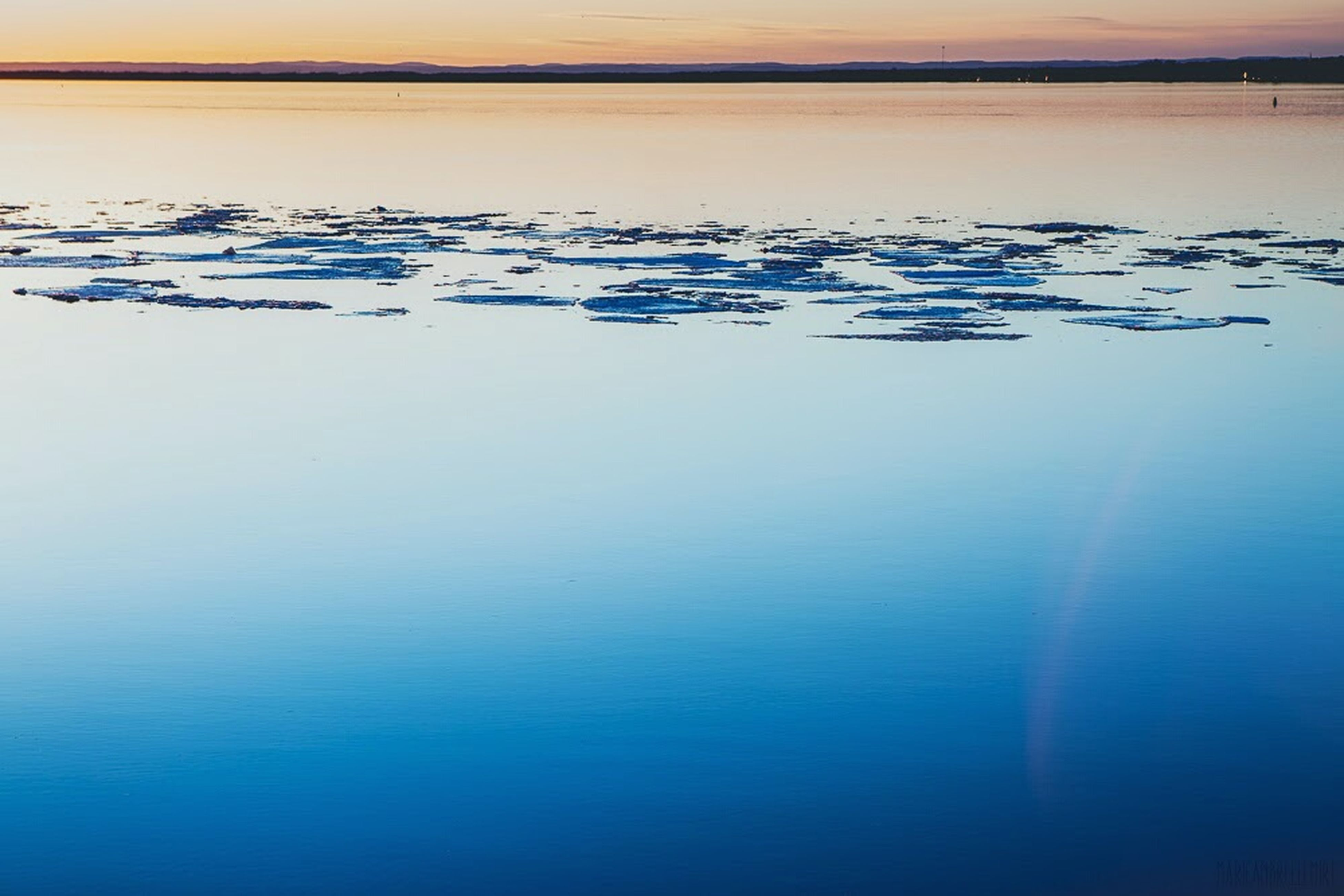 water, sea, tranquil scene, waterfront, tranquility, scenics, beauty in nature, sunset, nature, horizon over water, reflection, idyllic, sky, blue, calm, outdoors, no people, rippled, dusk, lake
