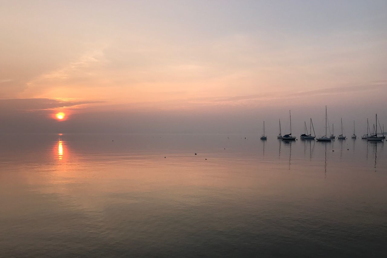 sunset, water, sea, scenics, tranquil scene, nature, beauty in nature, tranquility, reflection, nautical vessel, sky, idyllic, waterfront, no people, sun, transportation, outdoors, travel destinations, cloud - sky, horizon over water, sailboat, moored, day
