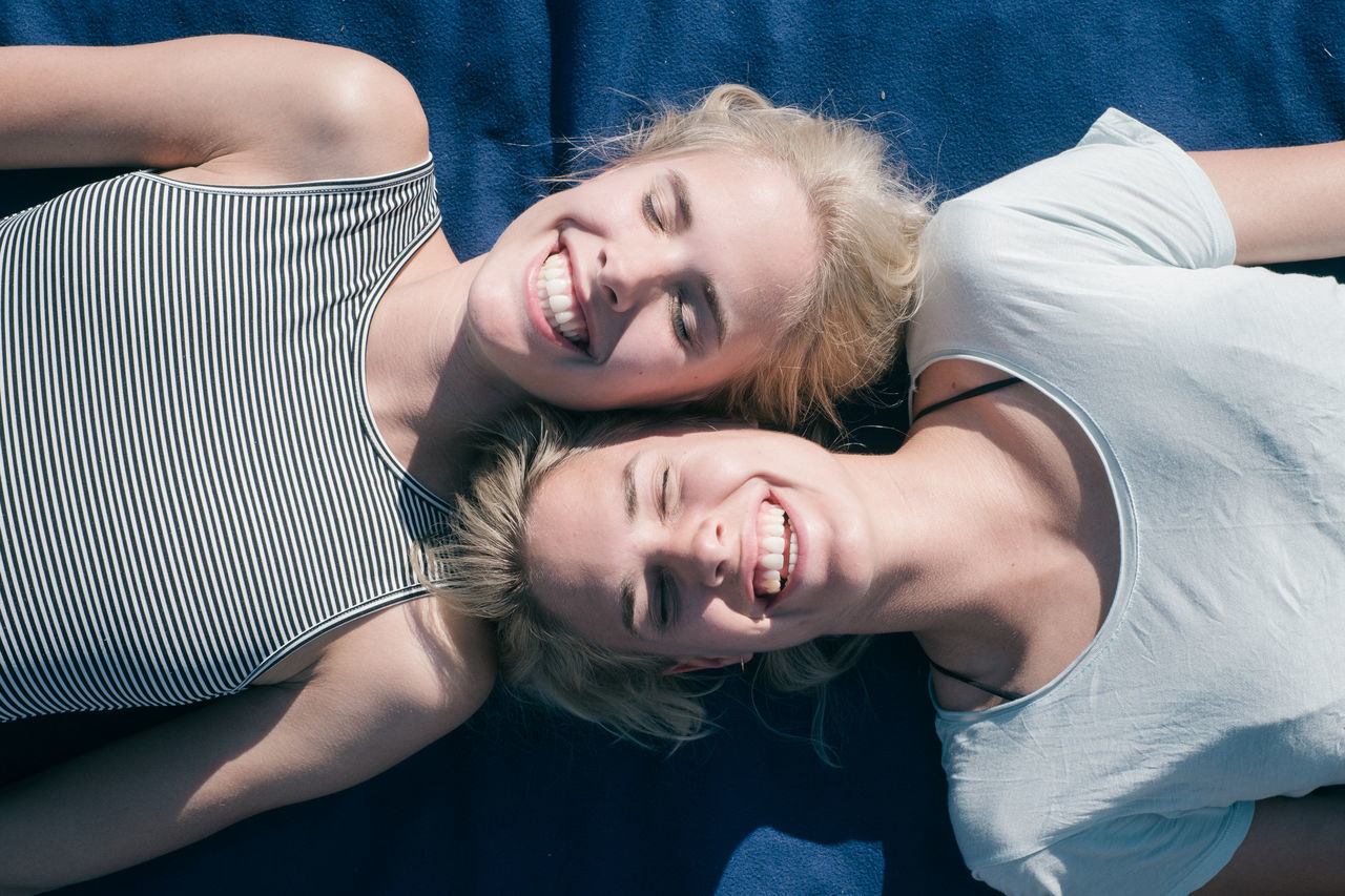 smiling, happiness, young adult, leisure activity, young women, fun, two people, real people, looking at camera, togetherness, lifestyles, portrait, home interior, young men, bonding, cheerful, indoors, friendship, blond hair, day