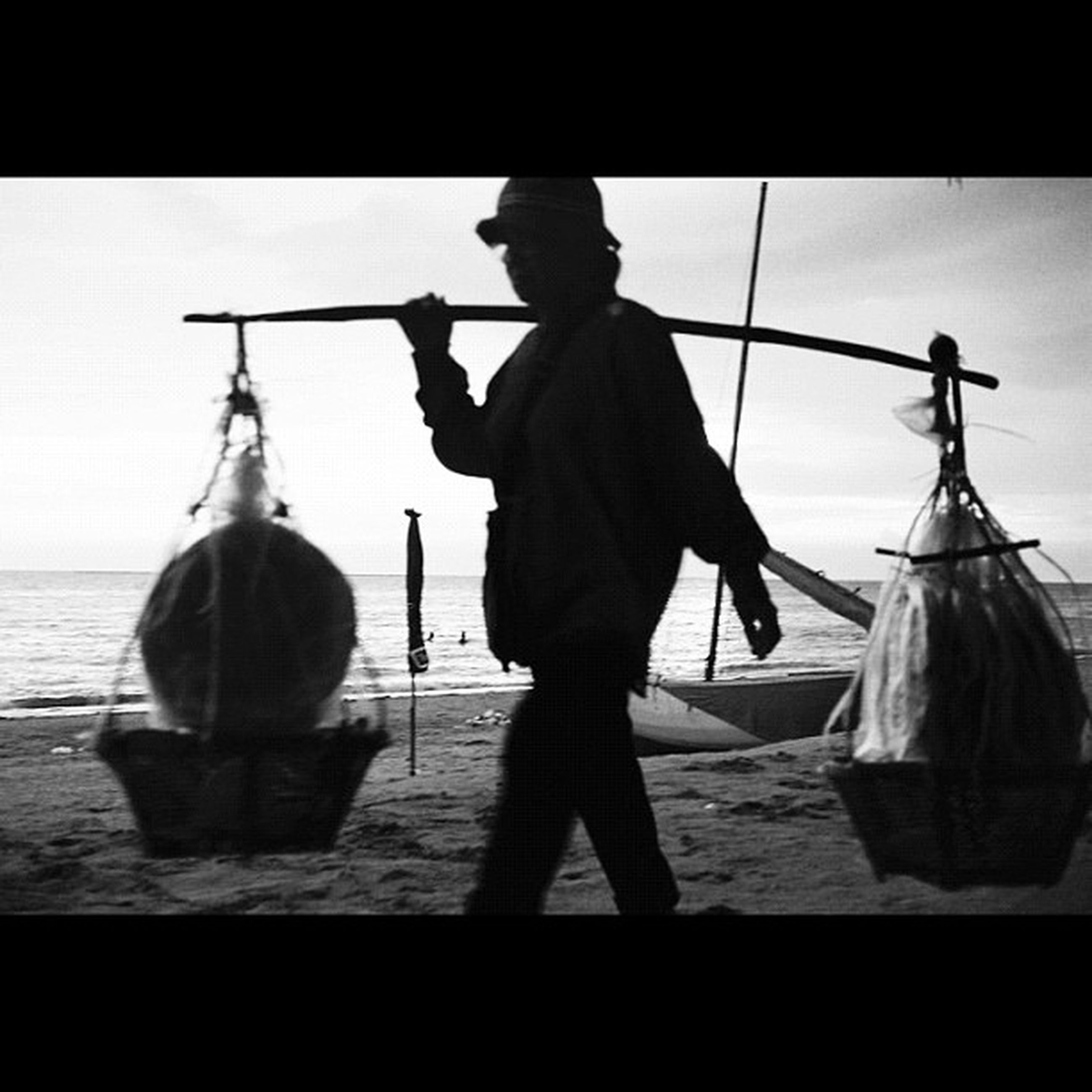 men, sea, transfer print, water, lifestyles, full length, leisure activity, rear view, auto post production filter, silhouette, sky, nautical vessel, person, holding, standing, occupation, transportation